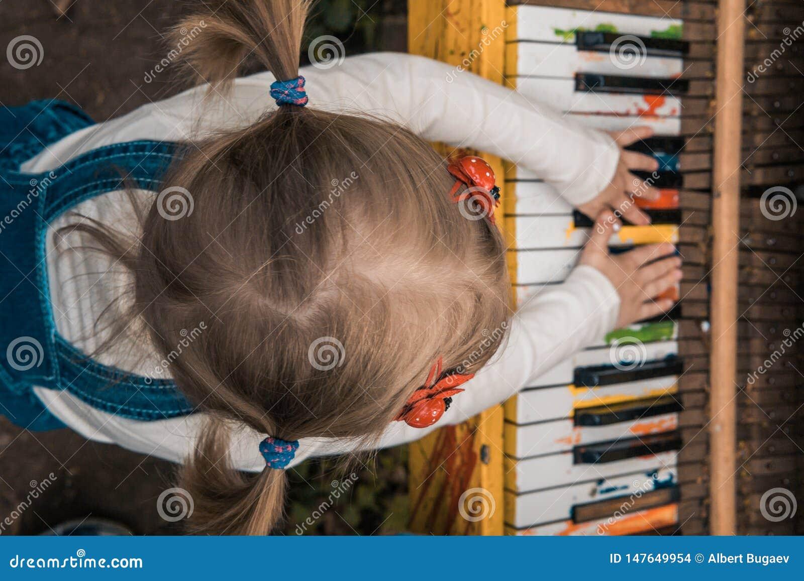 Het meisje speelt de kleurenpiano Children& x27; s handen De sleutels van de piano