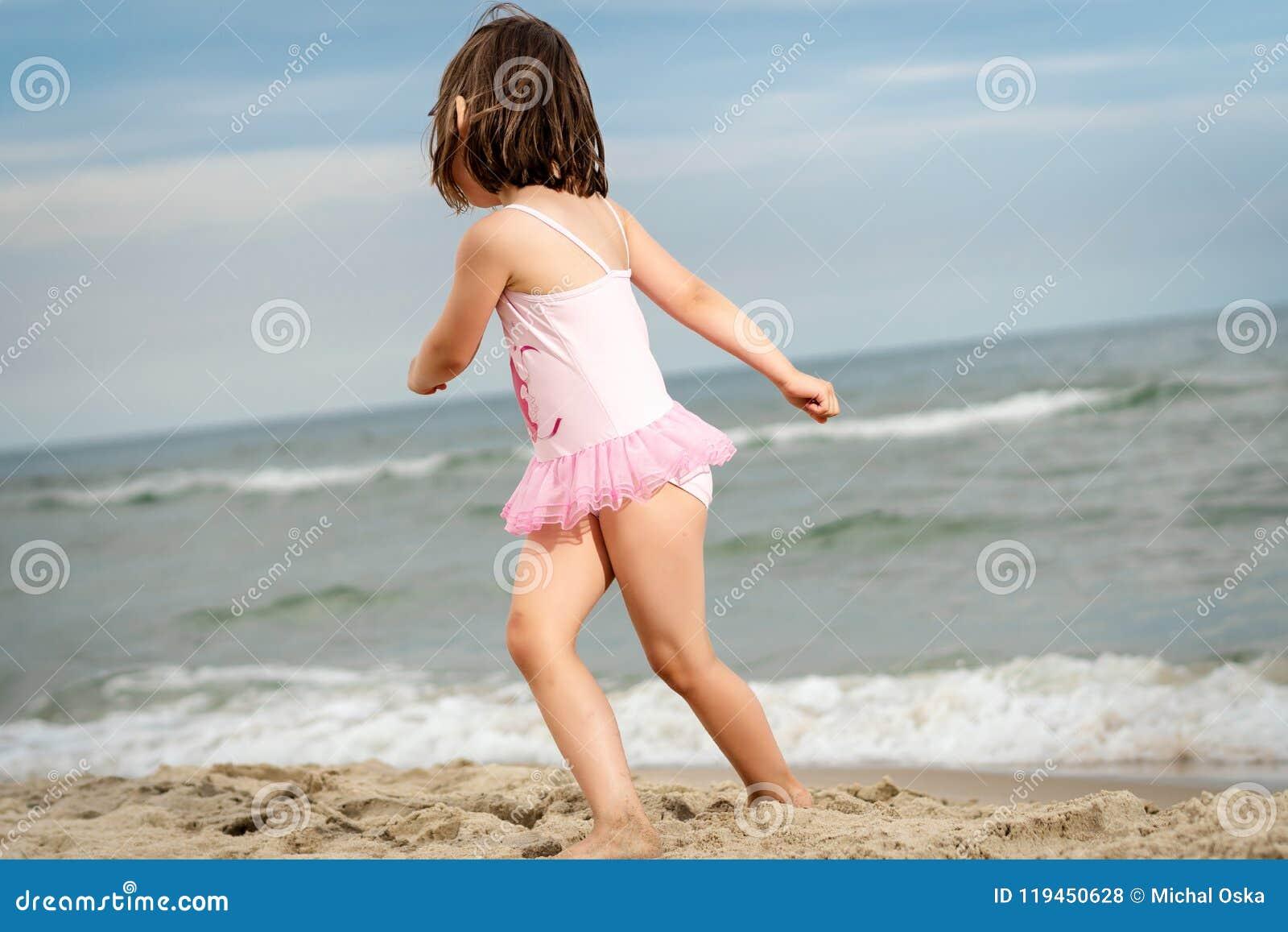 Het meisje speelt op het zand bij het strand