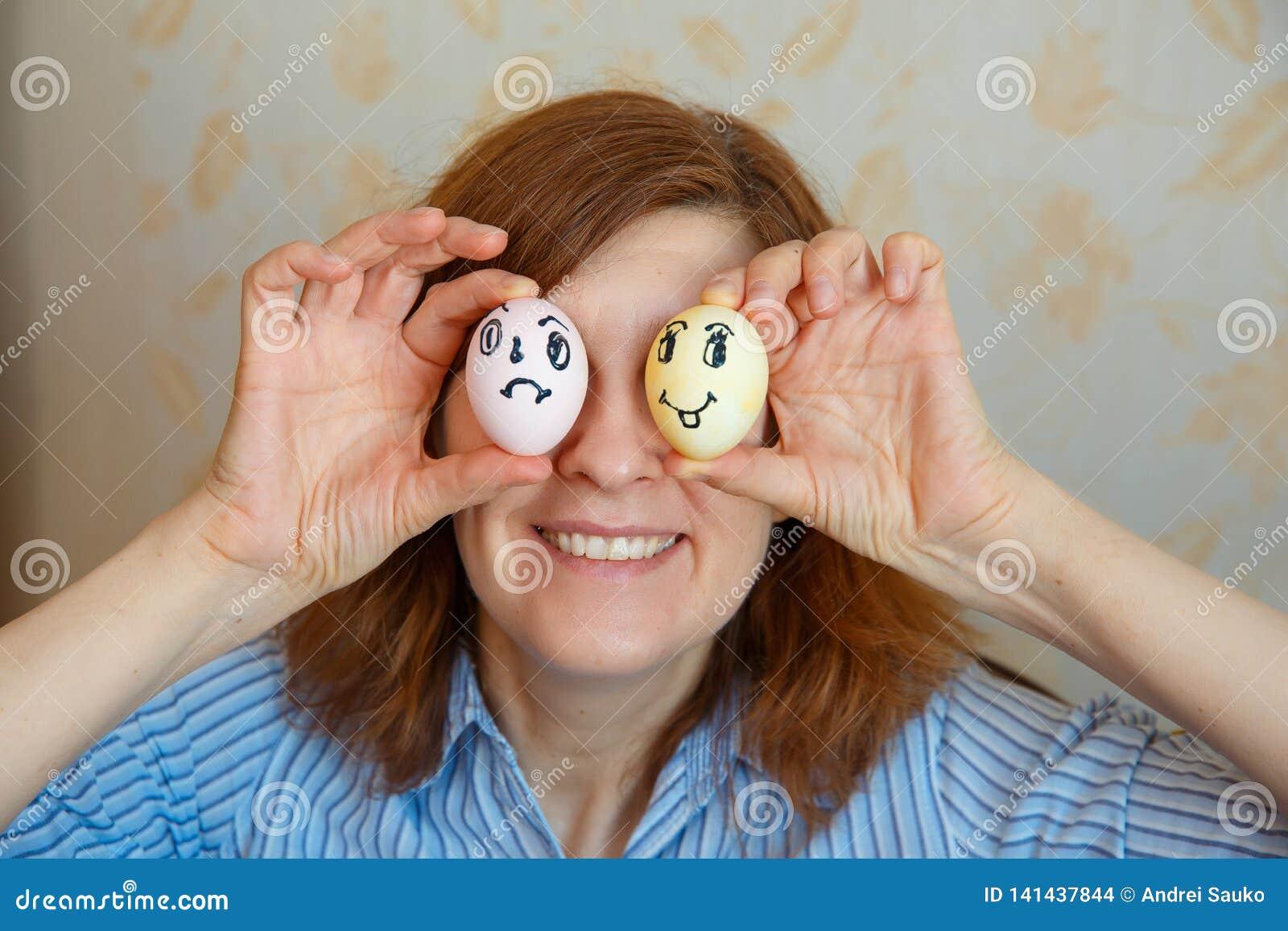 Het meisje toont geschilderde eieren voor Pasen met grappige gezichten