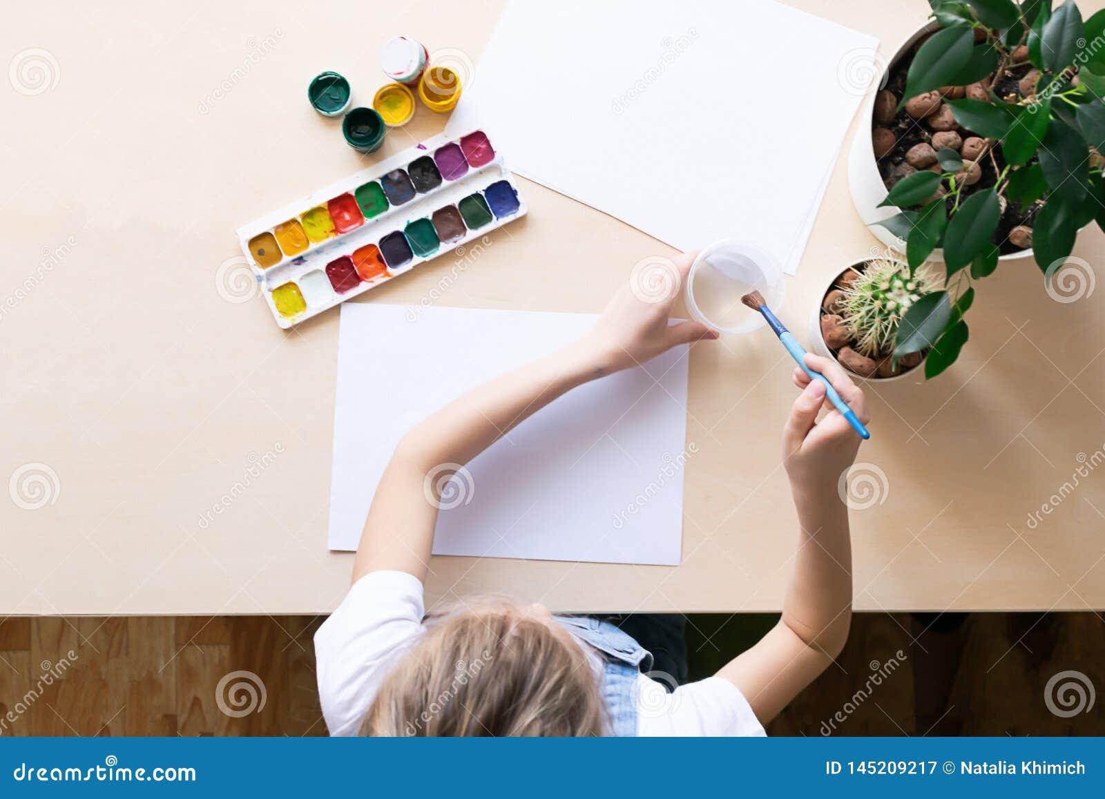 Het meisje trekt met gekleurde verven op Witboek bij de lijst Mening van hierboven Concept creativiteit en onderwijs