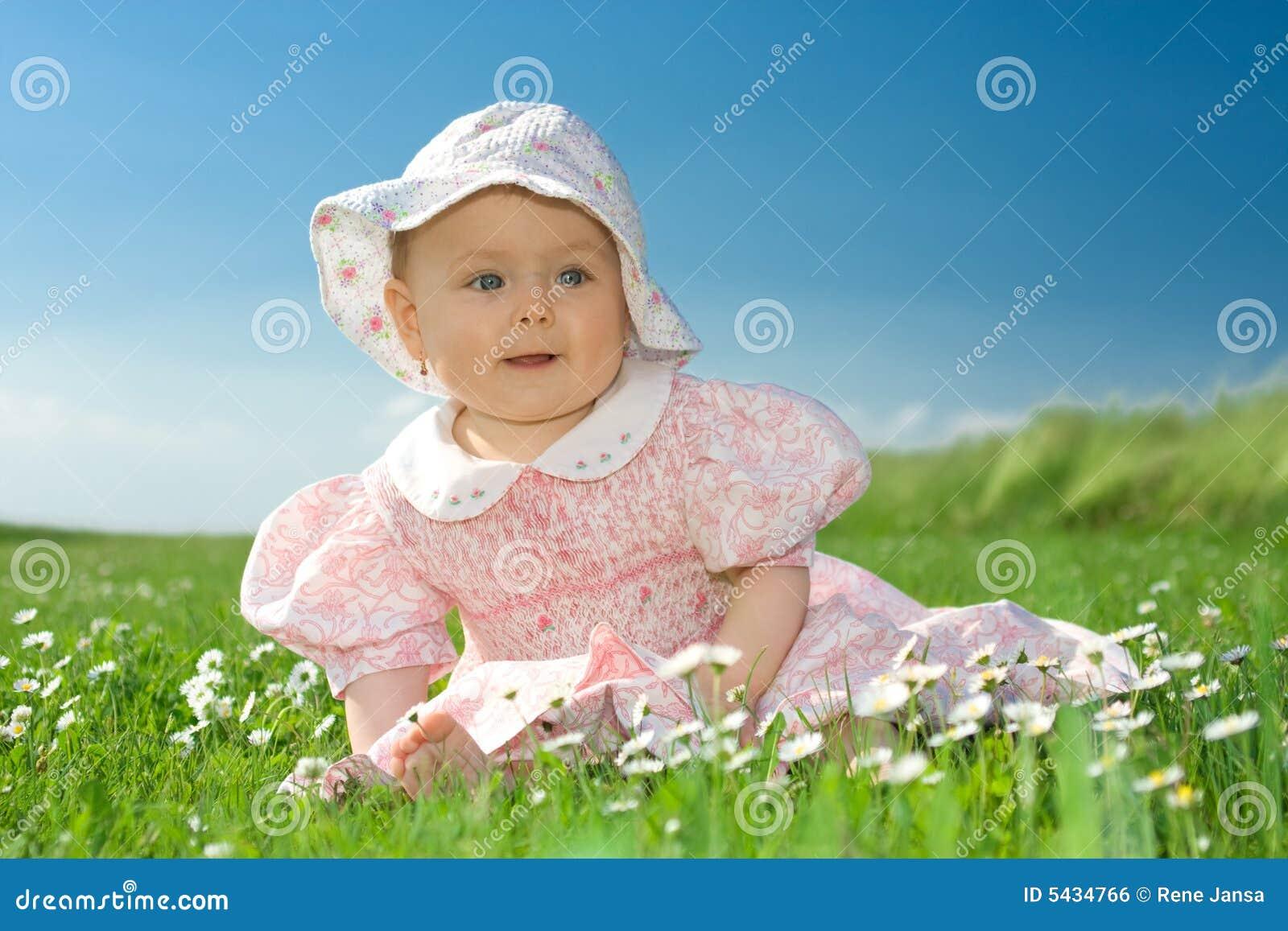 Het meisje van de baby dat op bloemrijk gebied wordt gezeten