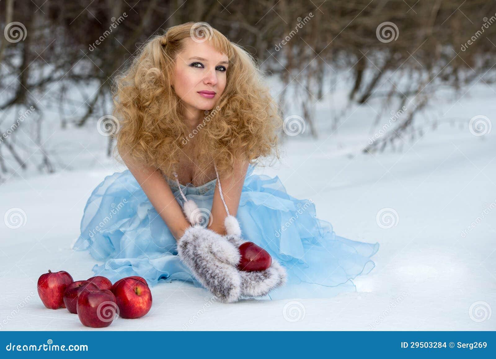 Het Meisje van de sneeuw in een de winterbos met appelen