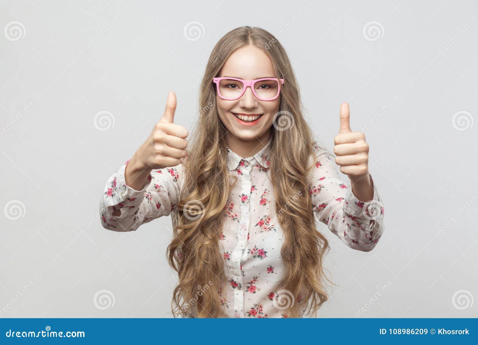 Het meisje van het gelukblonde in zonnebril, die duimen tonen, het kijken