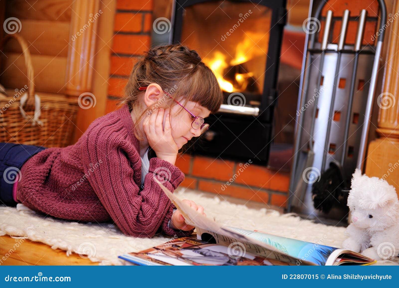 Het meisje van het kind leest voor open haard