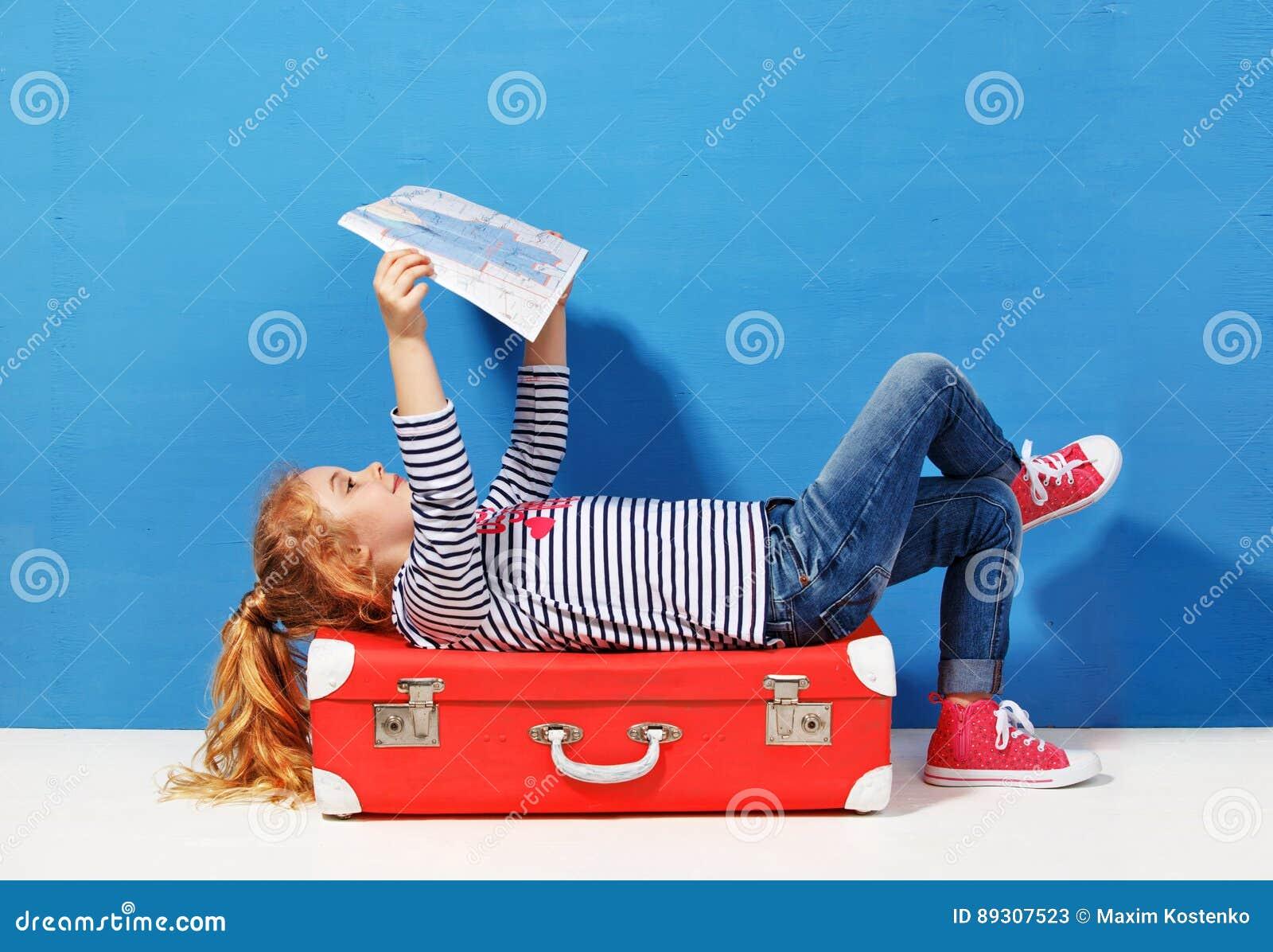 Het meisje van het kindblonde met roze uitstekende koffer en de stad brengen klaar voor de zomervakantie in kaart Reis en avontur