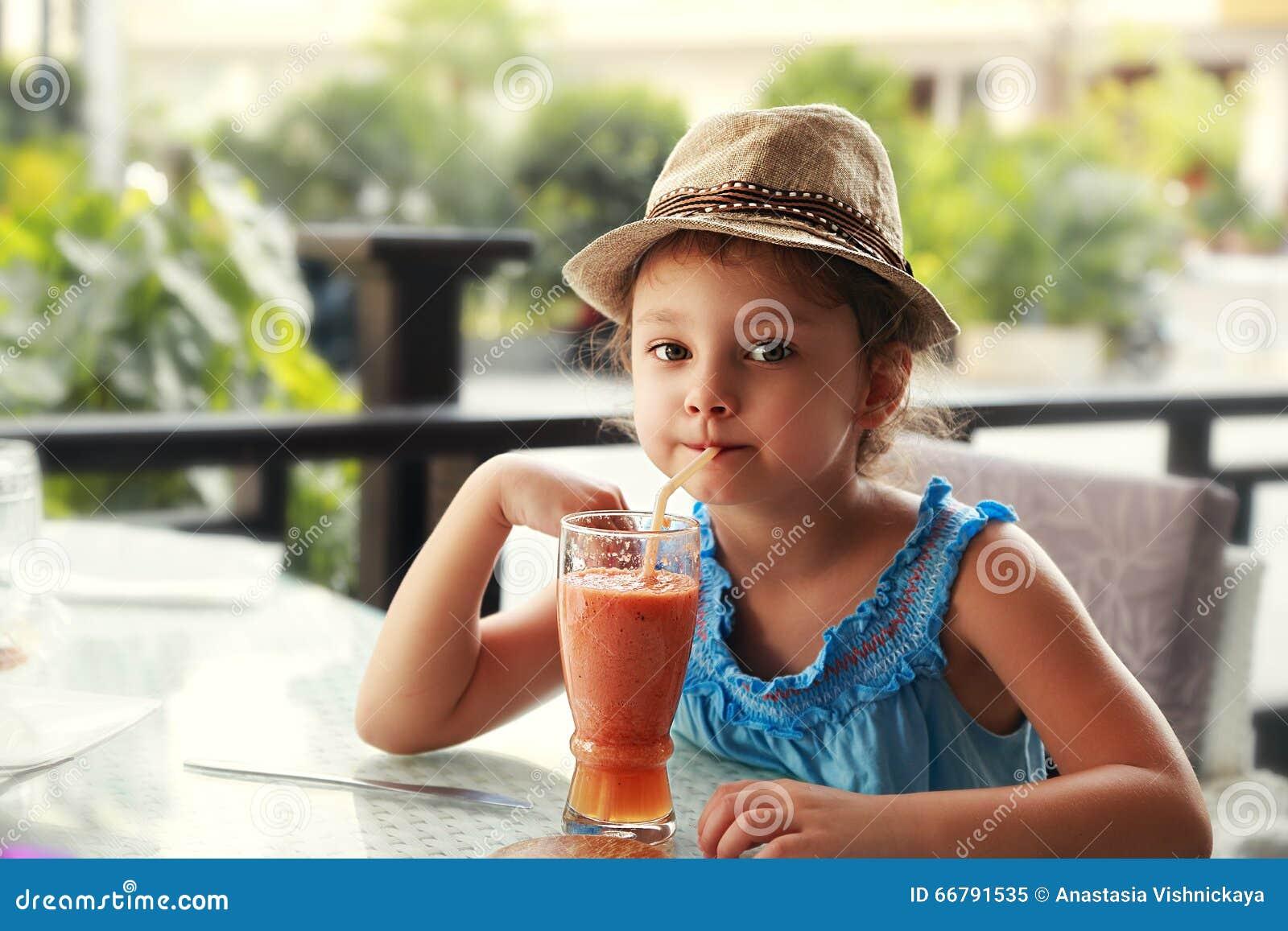 Het meisje van het pretjonge geitje in manierhoed het drinken smoothie sap in straat aangaande