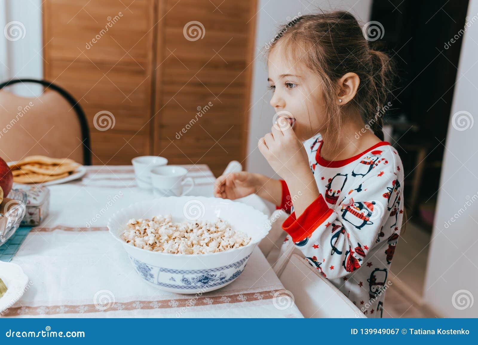 Het meisje van Nice gekleed in pyjama eet popcorn in keuken