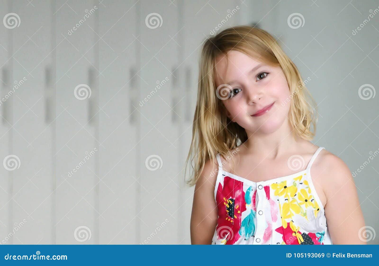 Het meisje van het zes éénjarigenblonde in een de zomer witte kleding met bloemen die op een abstracte achtergrond glimlachen