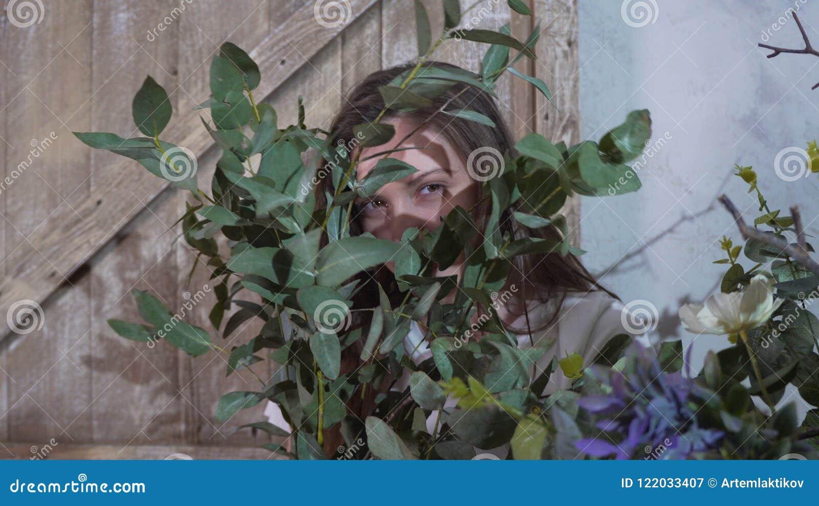 Het meisje verbergt haar ogen achter de bos van eucalyptus