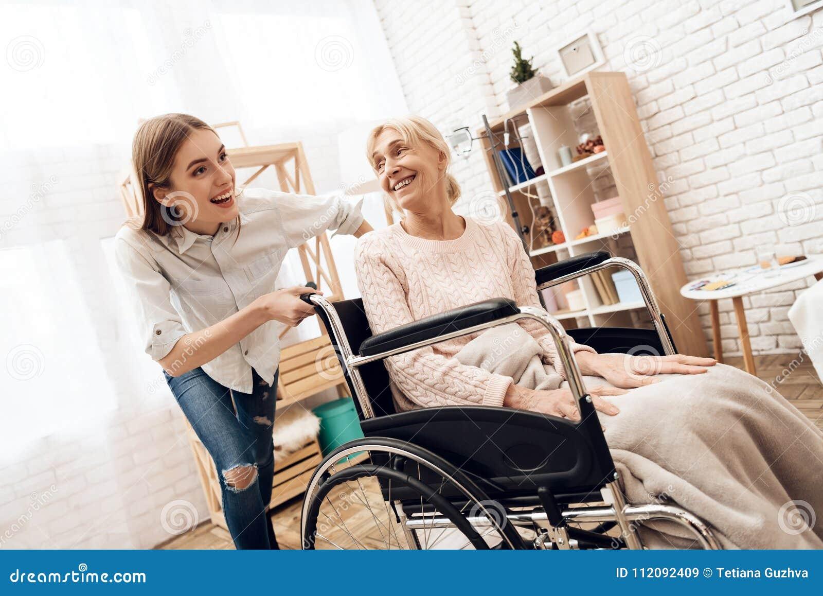 Het meisje verzorgt thuis bejaarde Het meisje berijdt vrouw in rolstoel