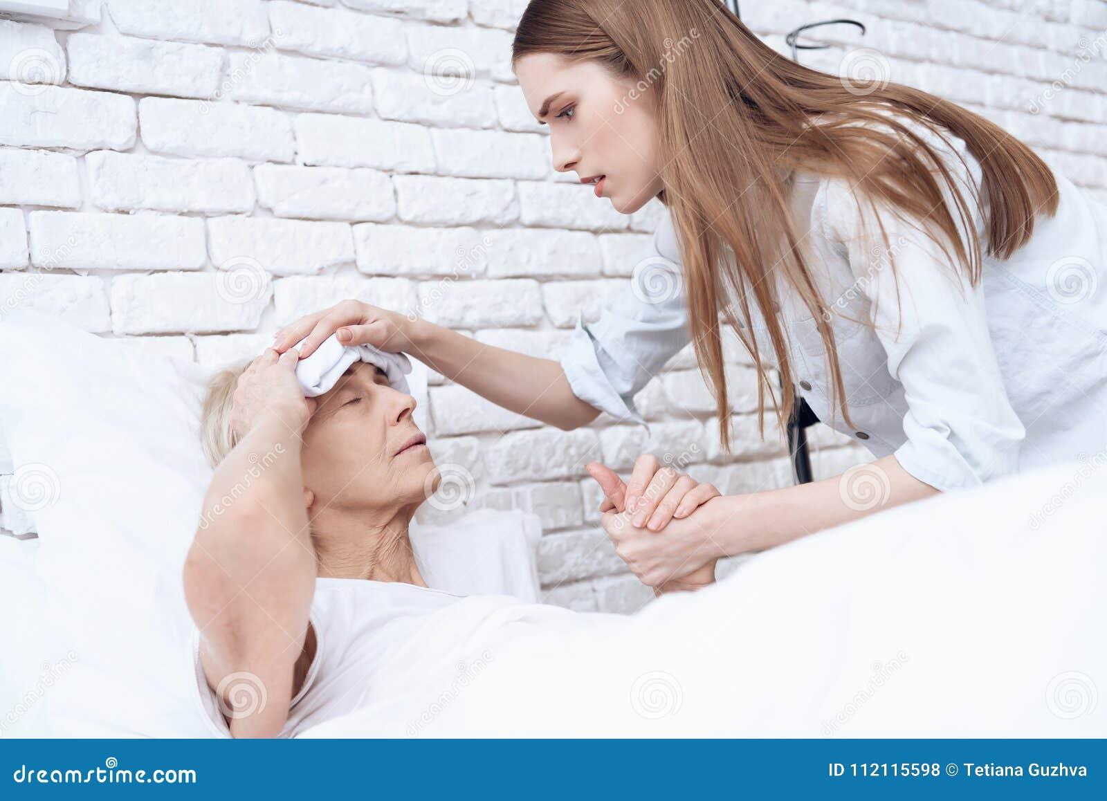 Het meisje verzorgt thuis bejaarde Zij houden handen De vrouw heeft kompres op haar hoofd