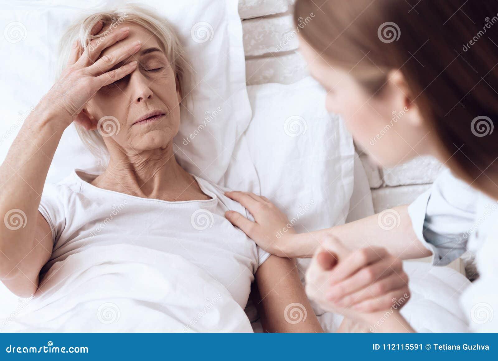 Het meisje verzorgt thuis bejaarde Zij houden handen De vrouw voelt slecht