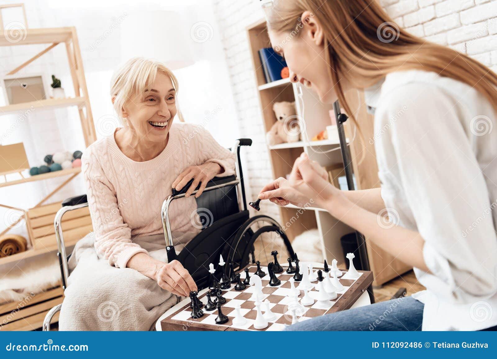 Het meisje verzorgt thuis bejaarde Zij spelen schaak