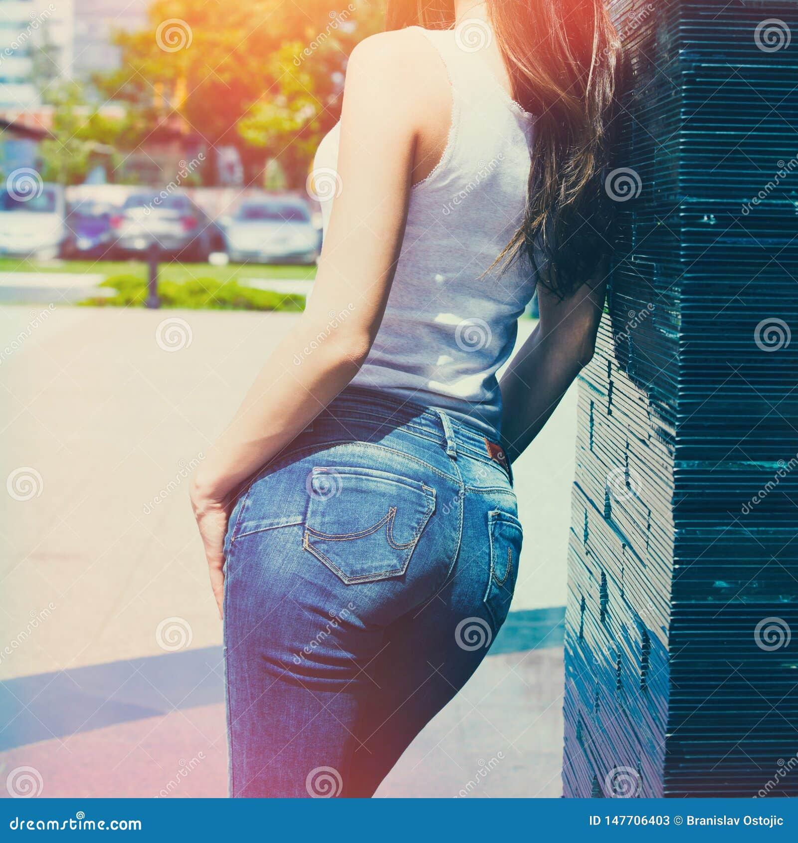 Het meisje in witte tankoverhemd en van de jeans openluchtzomer dag leunt op betegelde muur achtermening