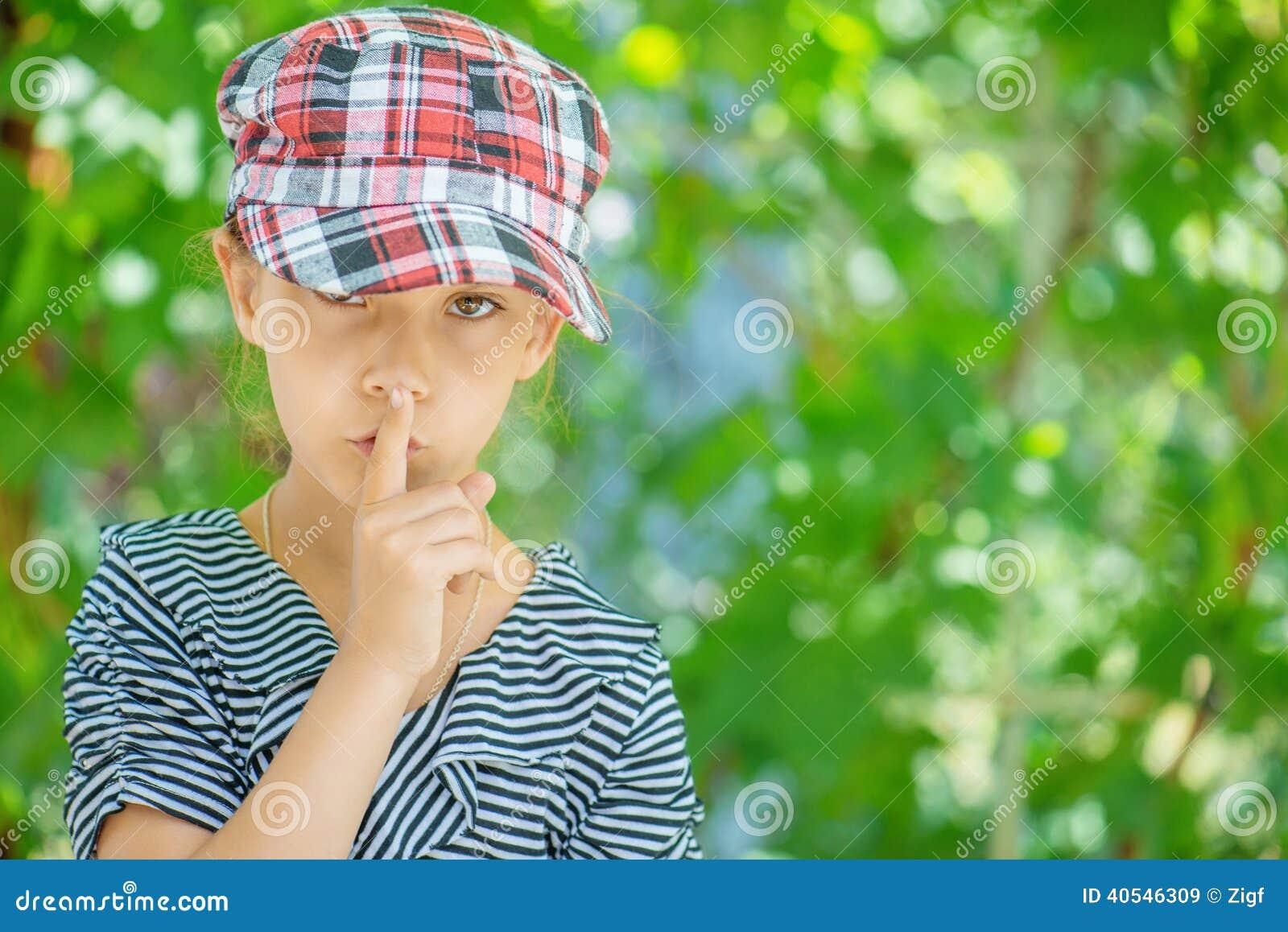 Het meisje zet wijsvinger aan lippen