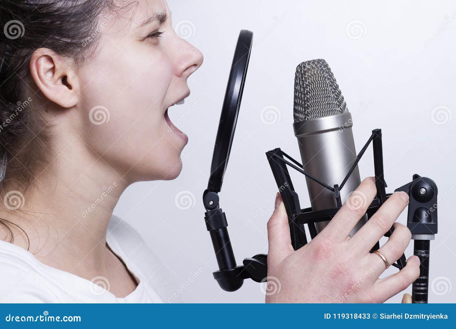 Het meisje zingt in de studiomicrofoon Het registreren van vocals van een jonge zanger