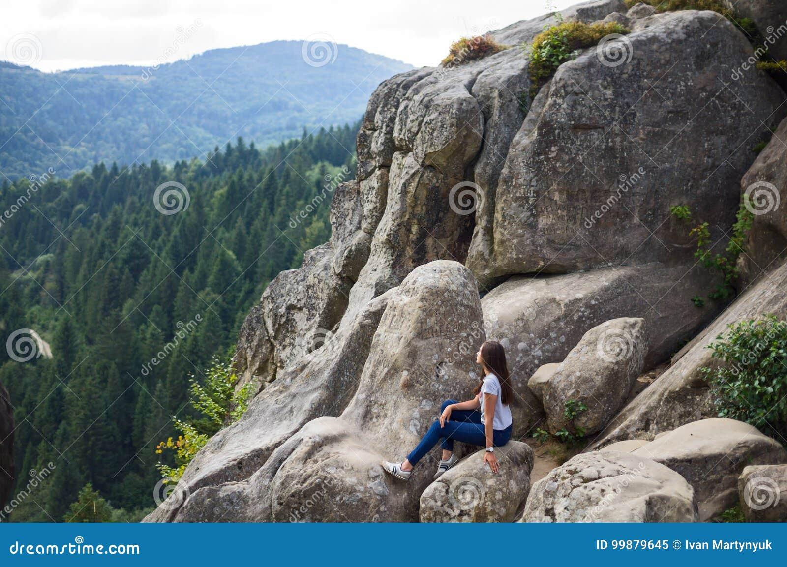 Het meisje zit op de rotsen