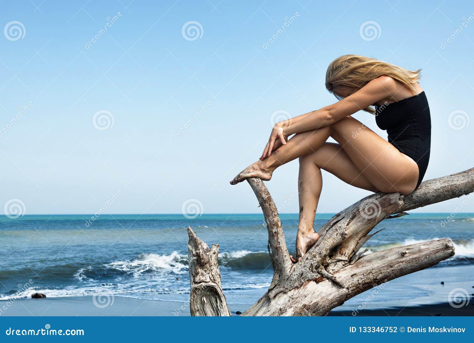 Het meisje zit op dode boomtak op zwart strand
