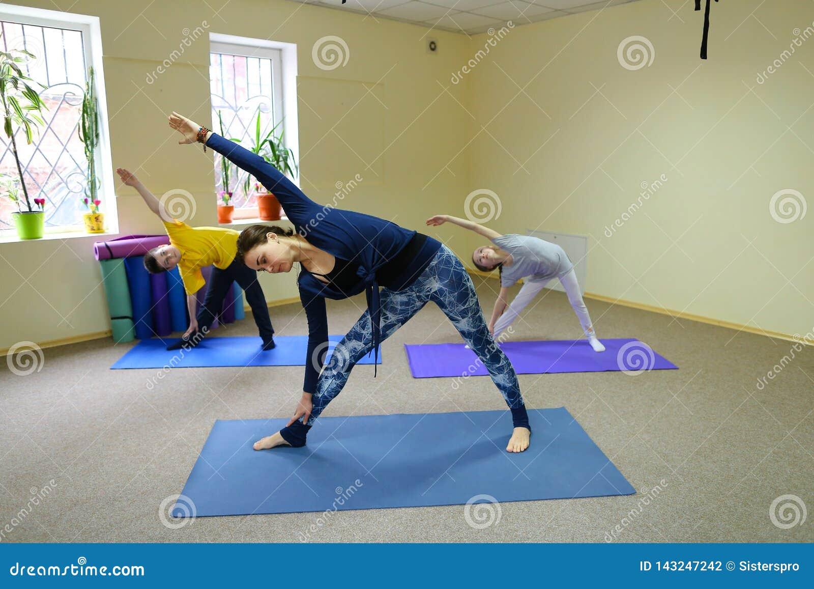 Het meisje zit op streng en de trainer helpt kind