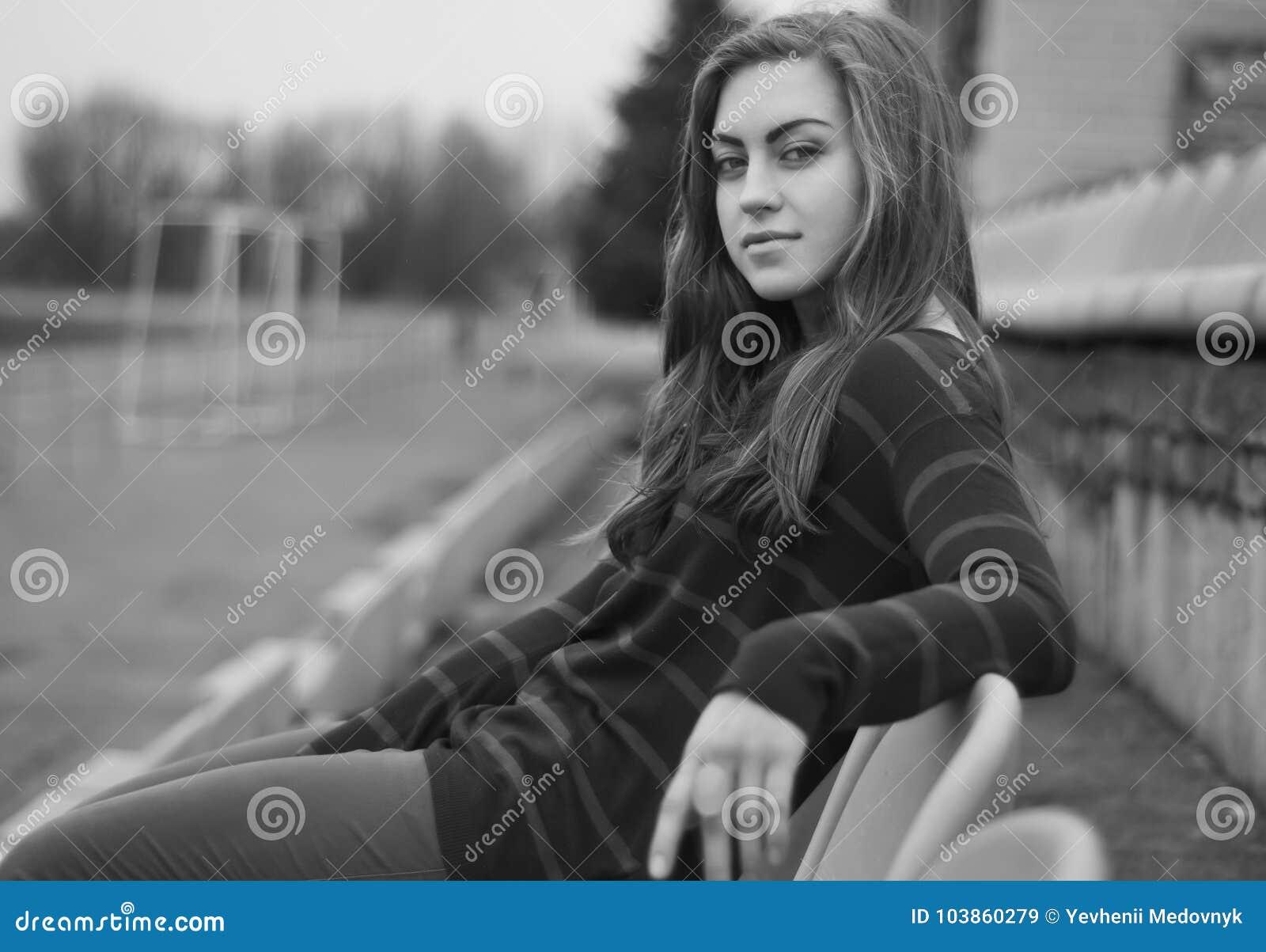 Het meisje zit stil op een stoel