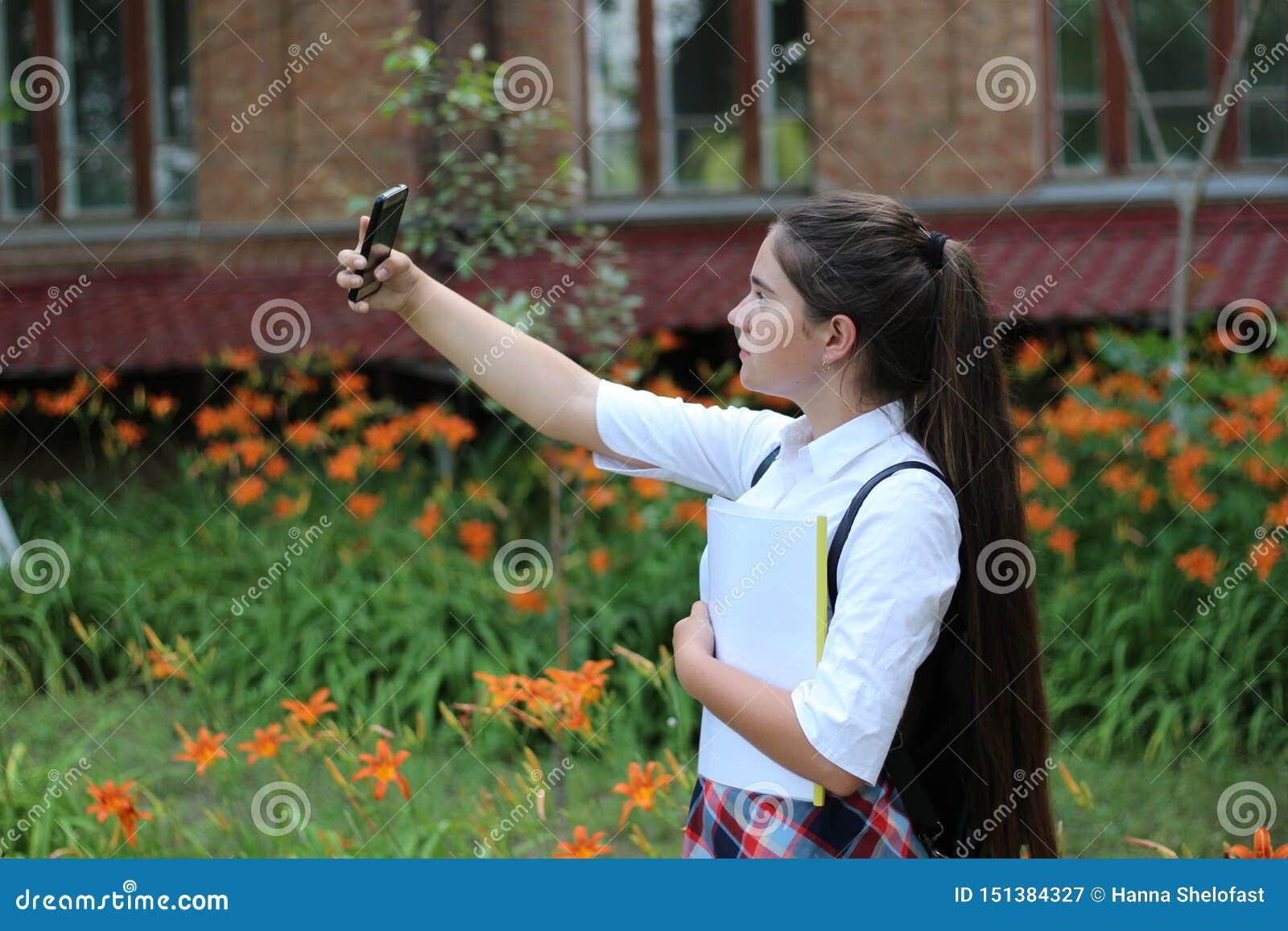 Het meisjesschoolmeisje met lang haar in eenvormige school maakt selfie