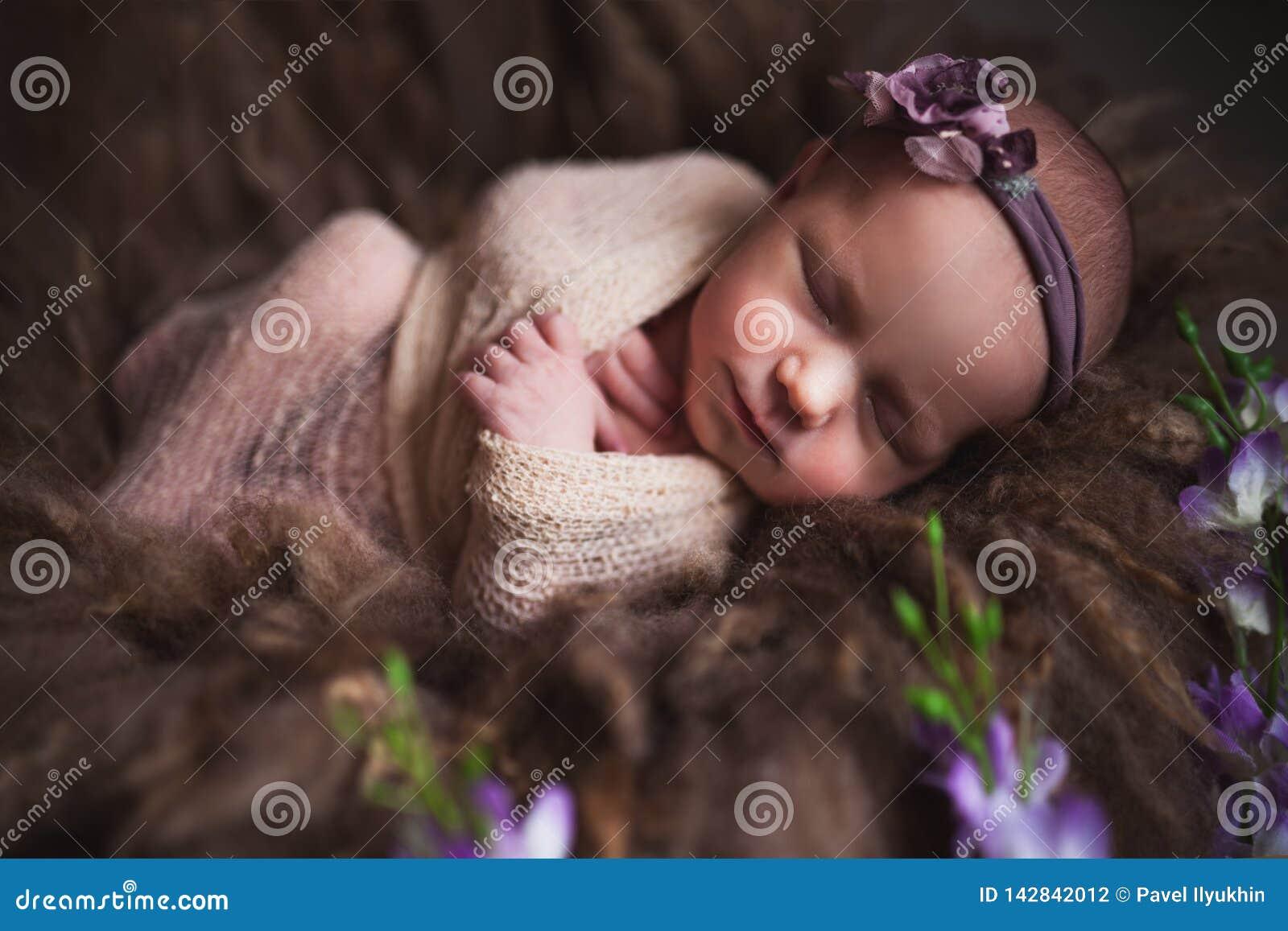 Het meisjesslaap van de zuigelingsbaby bij achtergrond Pasgeboren en mothercare concept