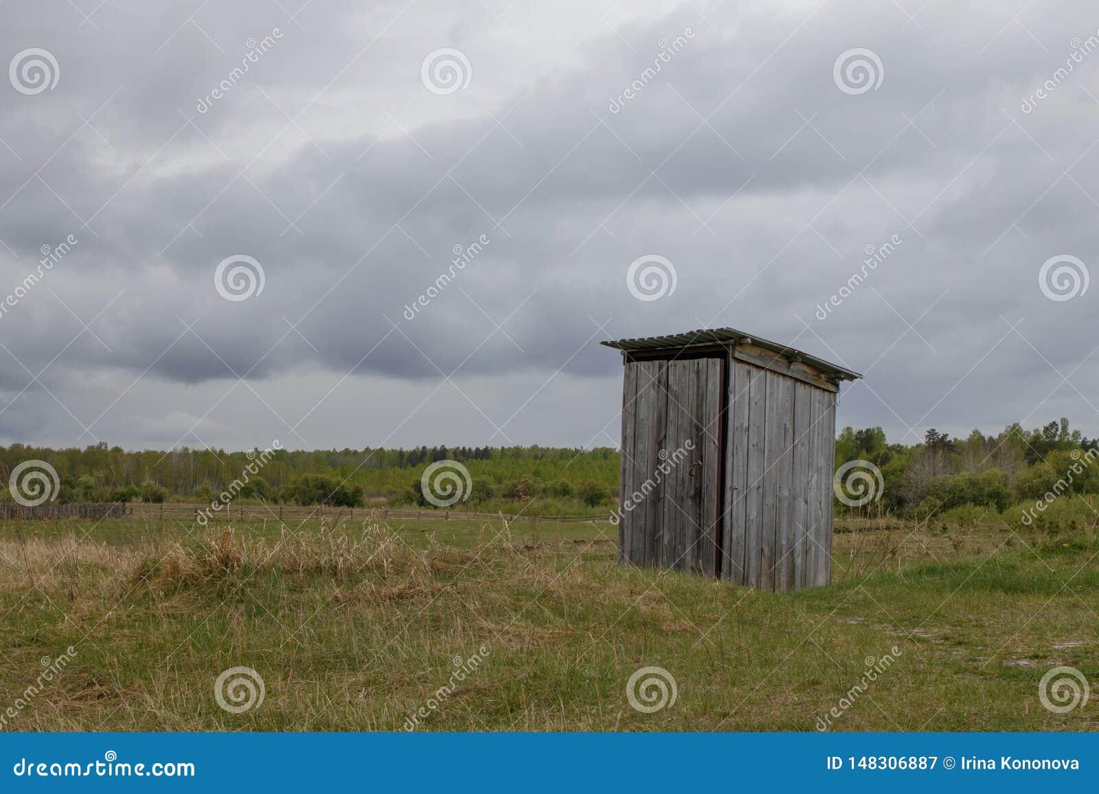 In het midden van de weidetribunes een rustiek openbaar toilet dat van houten planken wordt gemaakt
