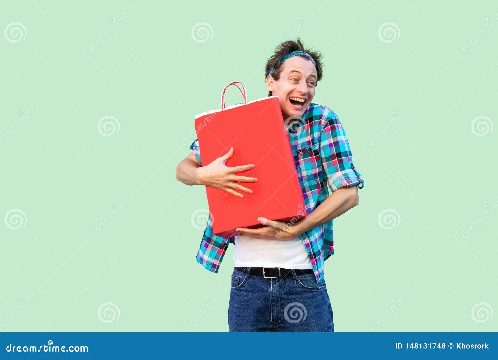 Het is mijn! De gekke gelukkige jonge volwassen shopoholic mens in witte t-shirt en geruite overhemd status, die het winkelen koe