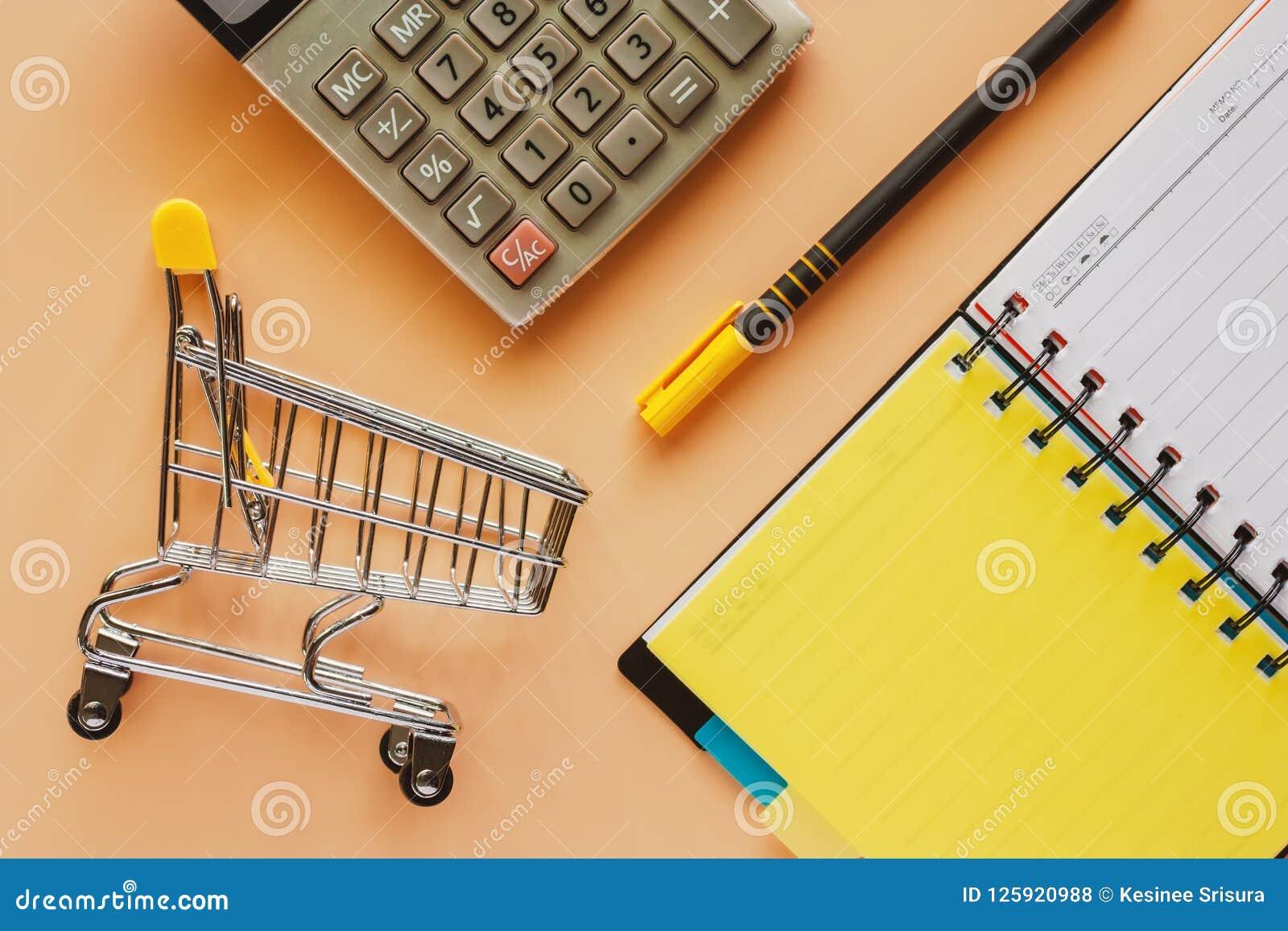 Het miniboodschappenwagentje of het karretje met geopend spiraalvormig notitieboekje, sluit a op