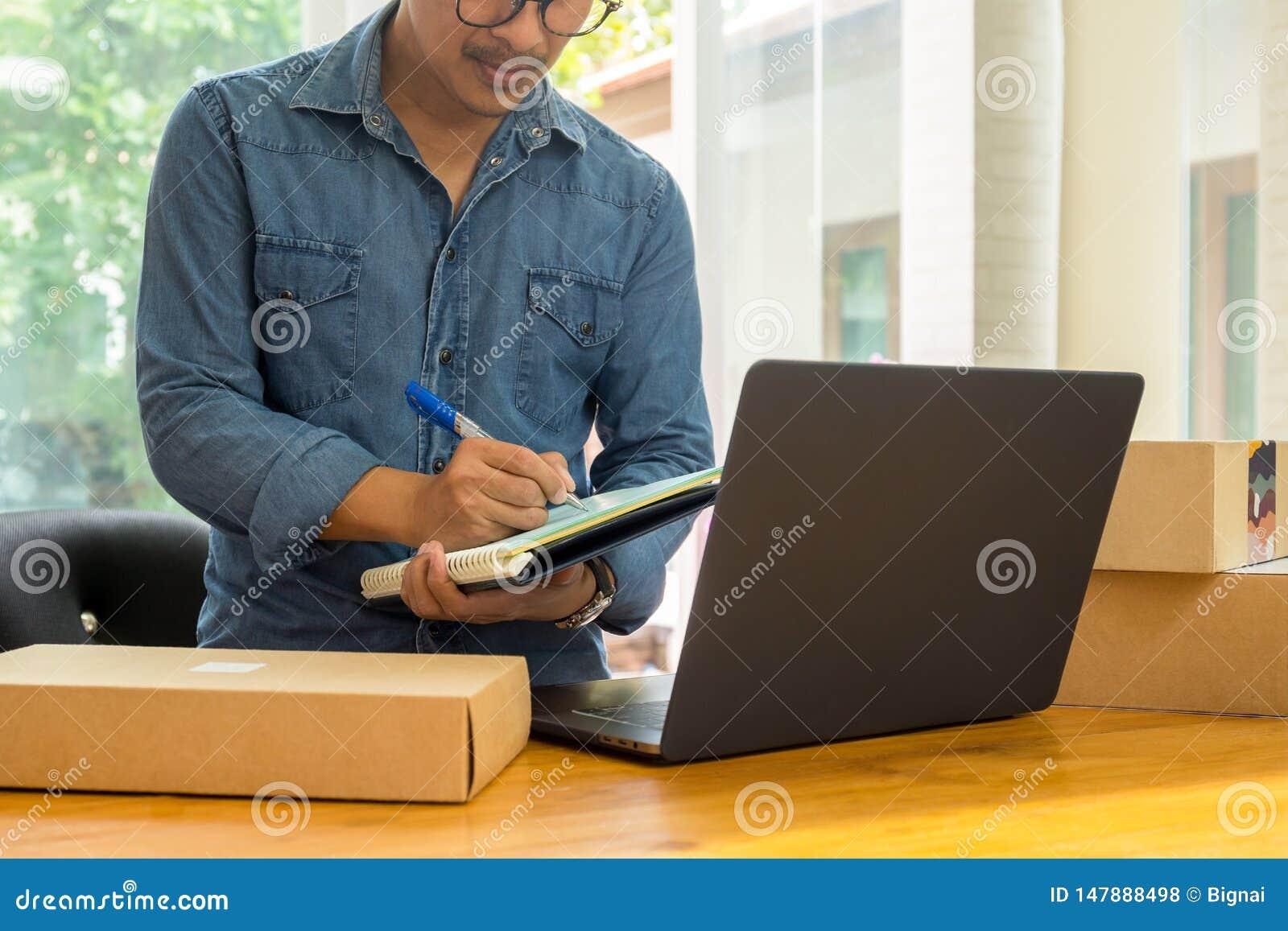 Het MKB-bedrijfseigenaars die inventaris met laptop controleren op de lijst