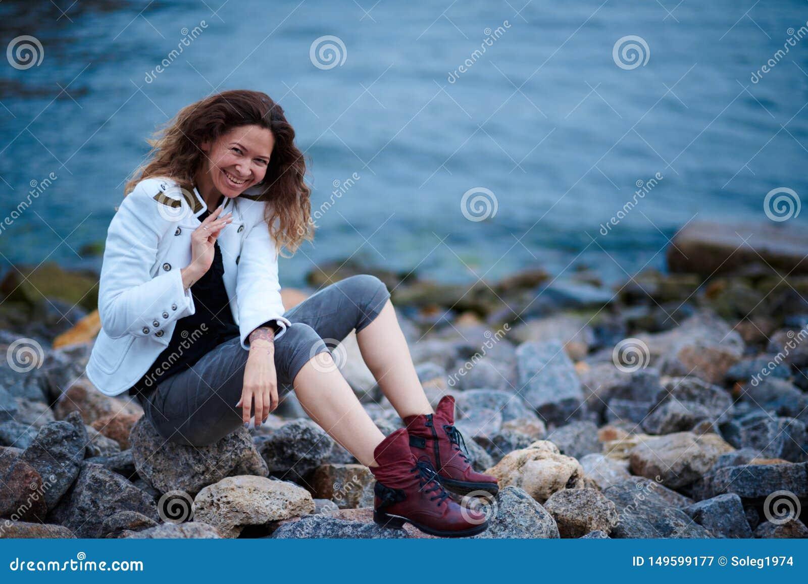 Het modieuze meisje kleedde zich in wit jasje en brede broeken die dichtbij overzees in de avond stellen
