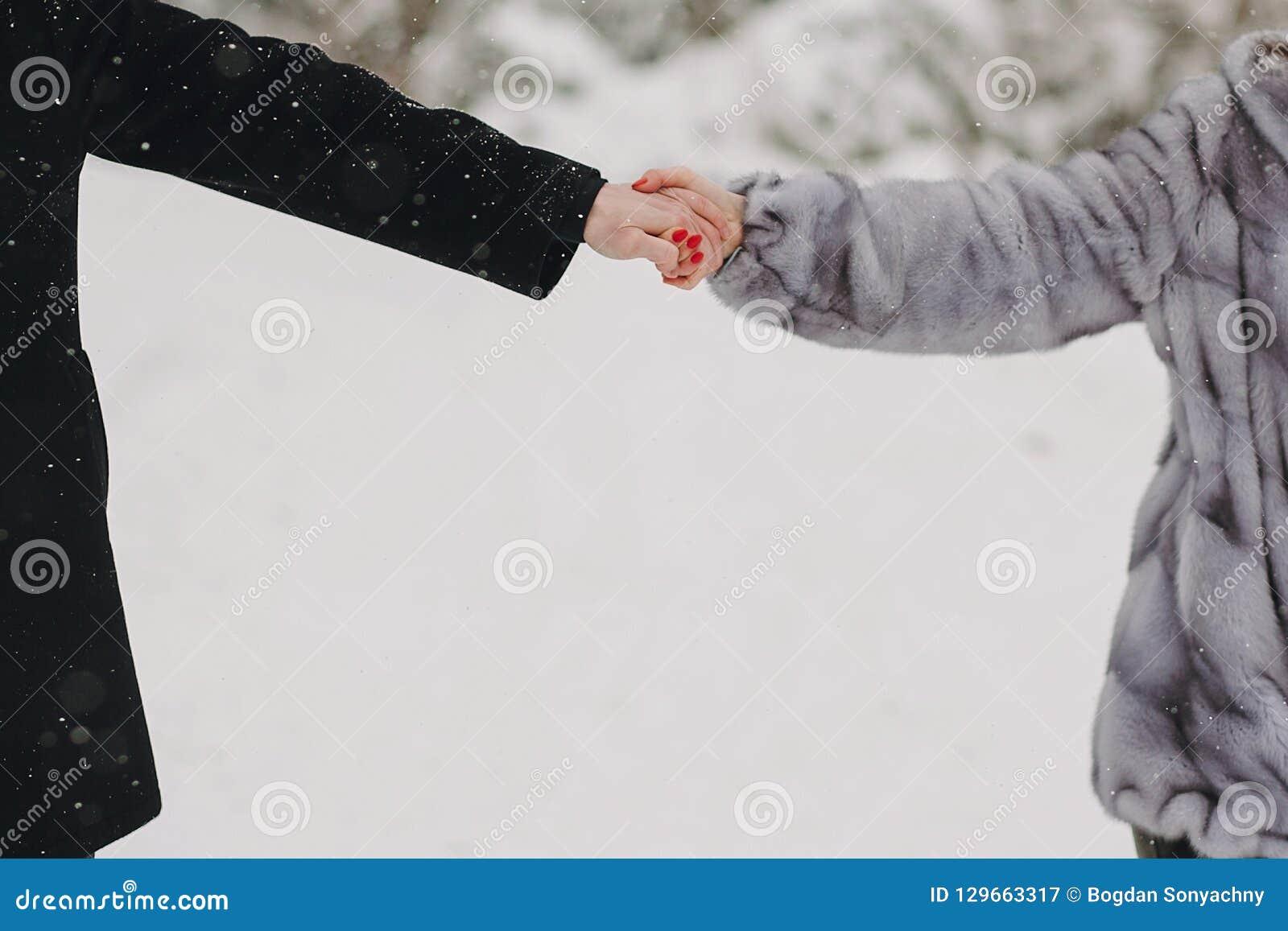 Het modieuze paar in pret hebben en liefde die dient sneeuwmou in houden