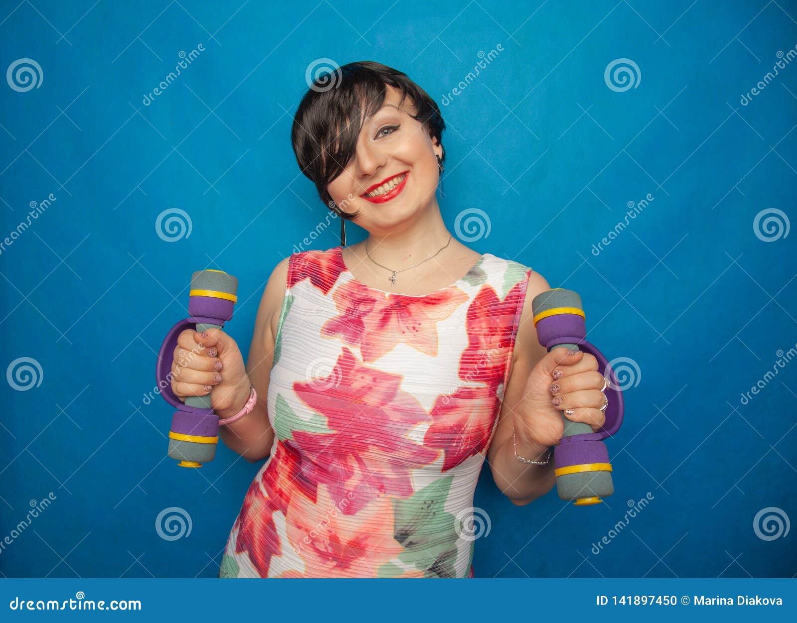 Het mollige blije emotionele meisje met kort haar probeert om sporten met domoren te doen gezond zijn en gewicht verliezen