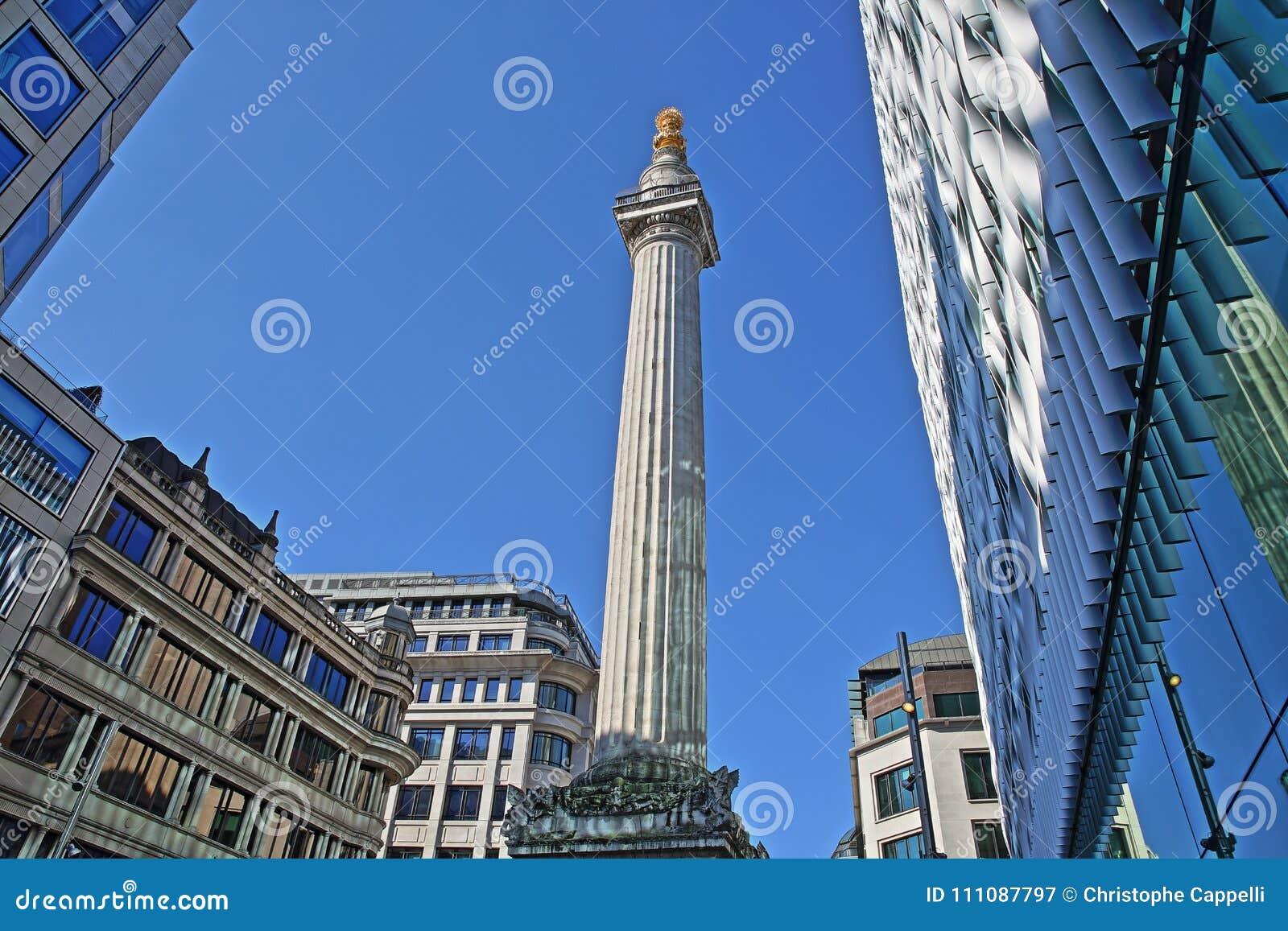 Het Monument aan de grote die brand in Londen door moderne gebouwen in het financiële district van de Stad van Londen wordt omrin