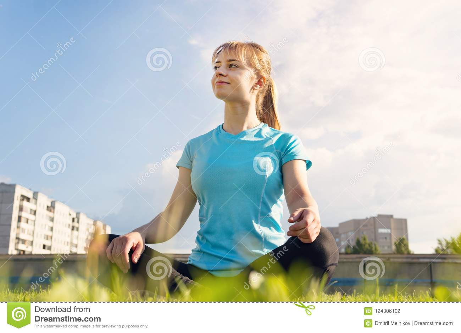 Het mooie aantrekkelijke jonge vrouw uitrekkende uitoefenen in het park Jonge volwassenen Het concept van de gezondheid Het conce