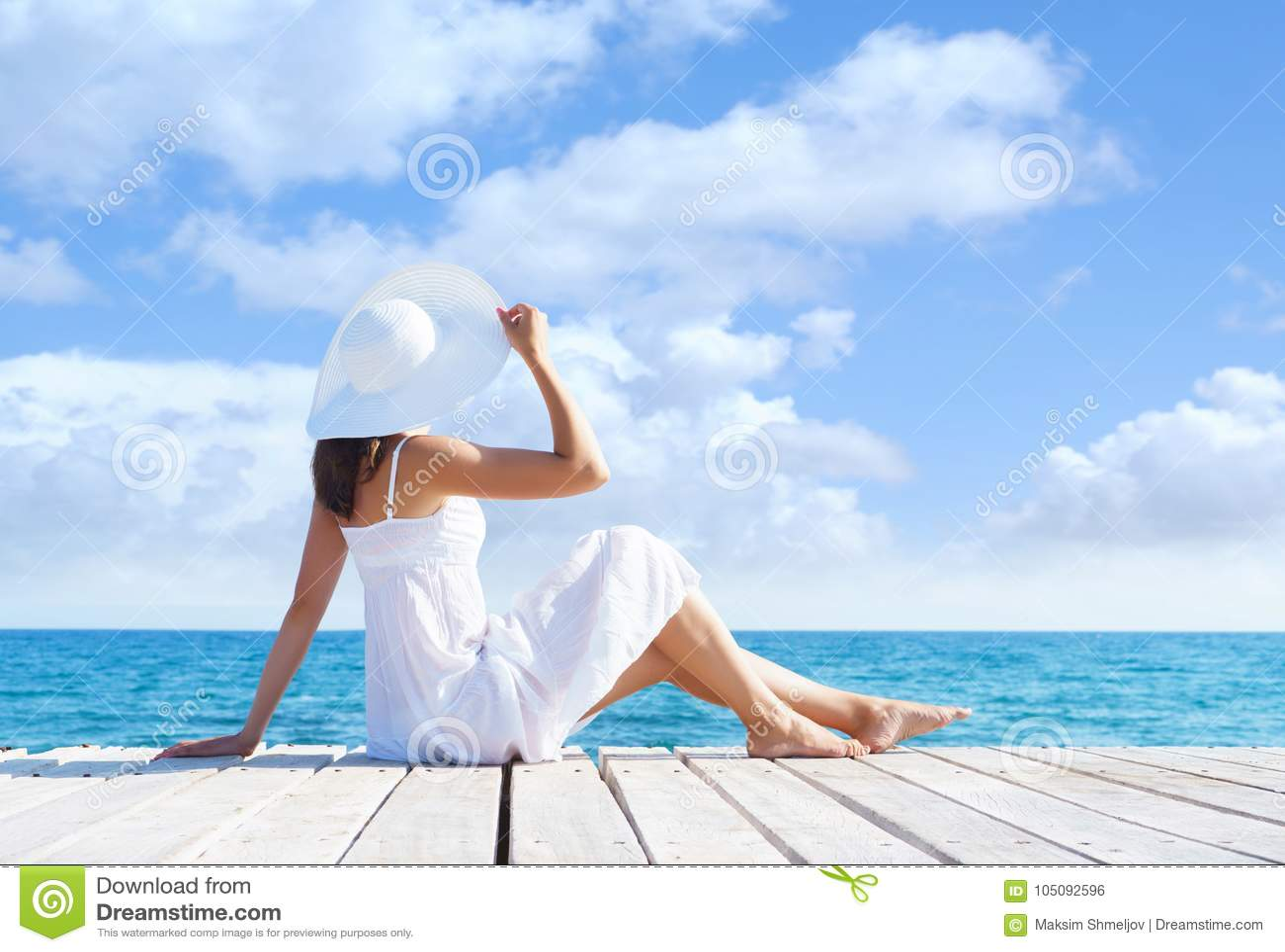Het mooie, aantrekkelijke model stellen in witte kleding op een houten pijler Overzeese en Hemelachtergrond Vakantie, die reizen