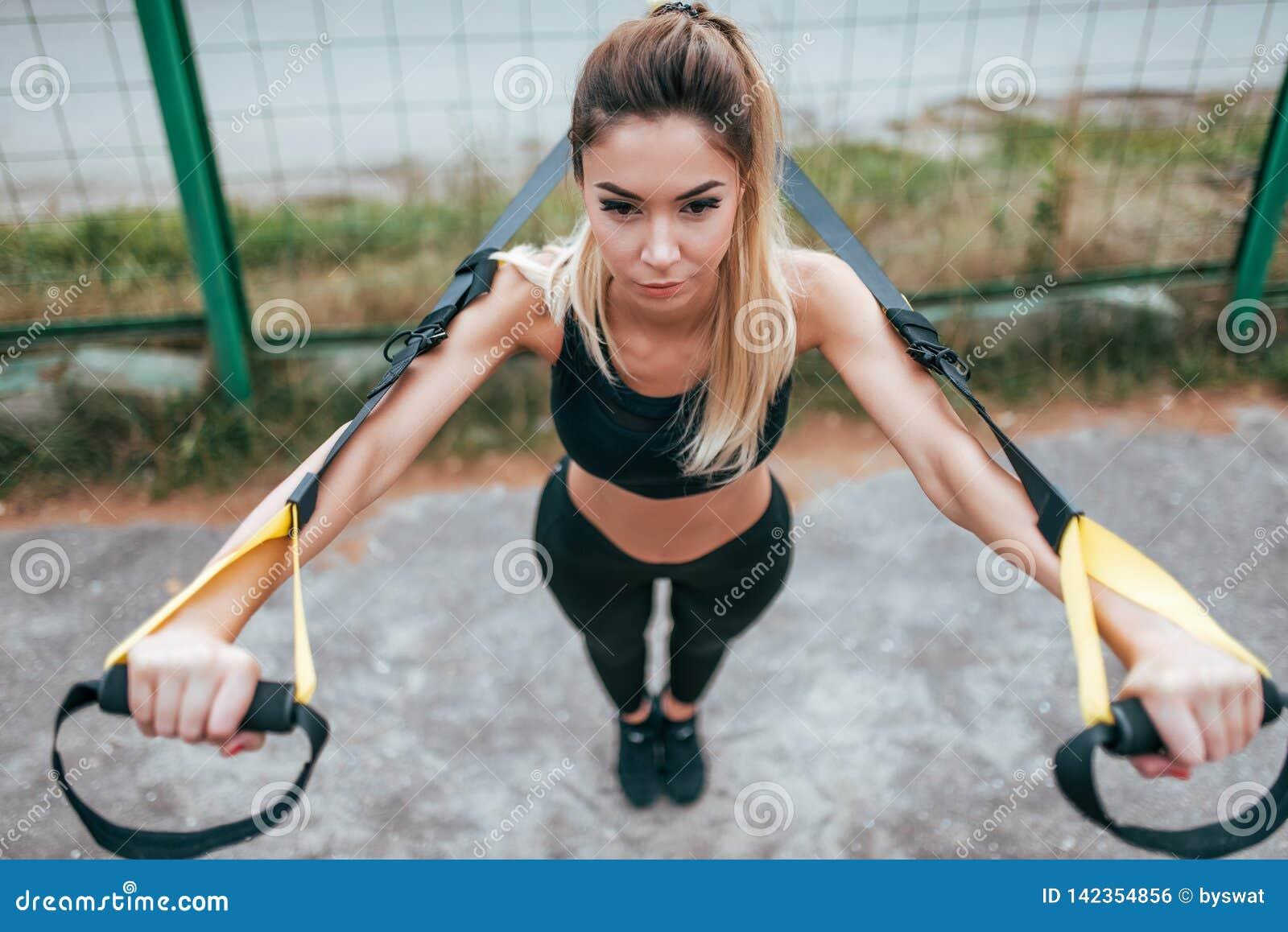 Het mooie atletenmeisje is scharnierend op de riemen, de bovenkant van sportkledingsbeenkappen In de zomer op de sportengrond in