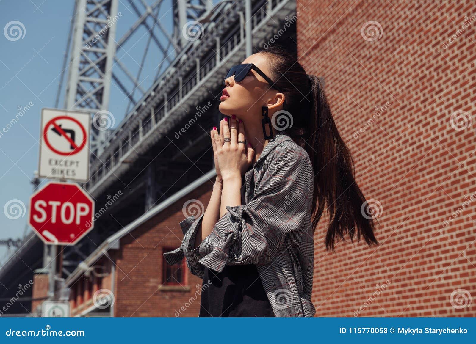 Het mooie Aziatische mannequinmeisje stellen op stadsstraat die modieuze denimkleren en zonnebril dragen