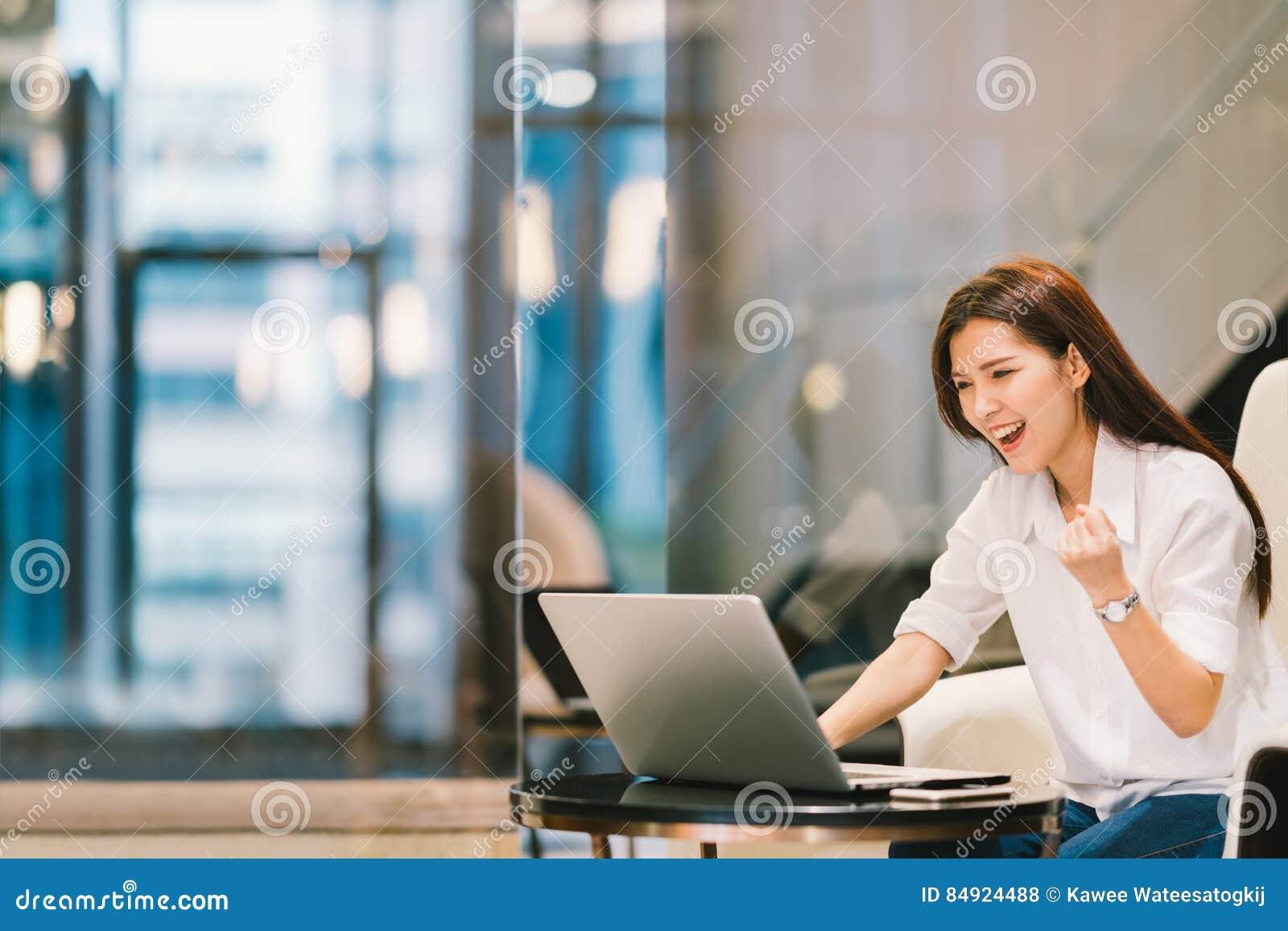 Het mooie Aziatische meisje viert met laptop, stelt het succes, onderwijs of technologie of start bedrijfsconcept, met exemplaarr