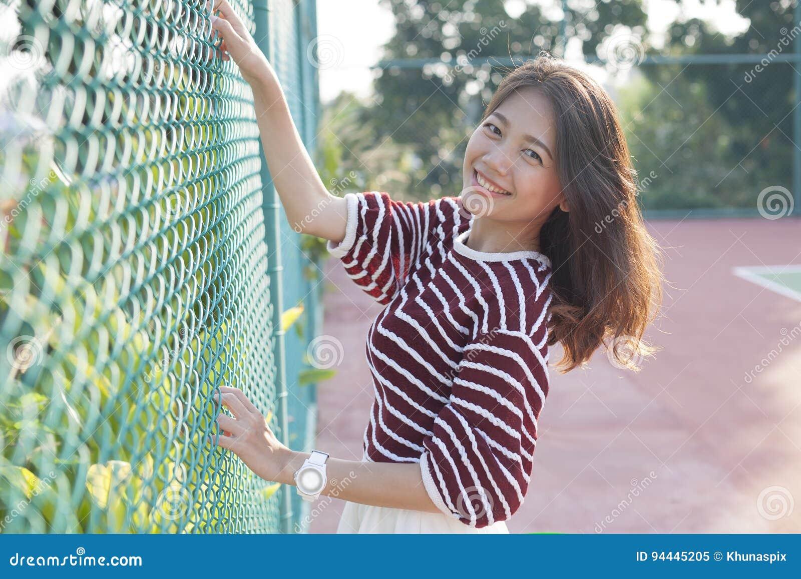 Het mooie Aziatische vrouw ontspannen, gelukvakantie in tennisspo