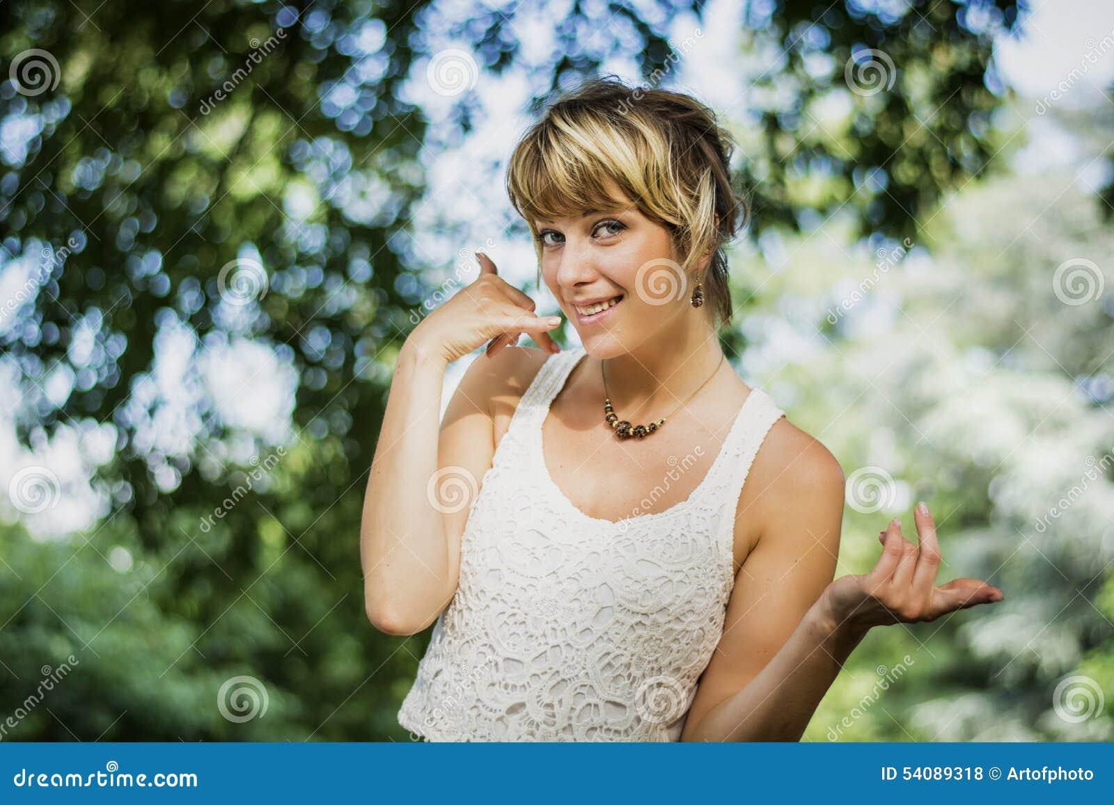 Het mooie blonde jonge vrouw doen roept me teken met