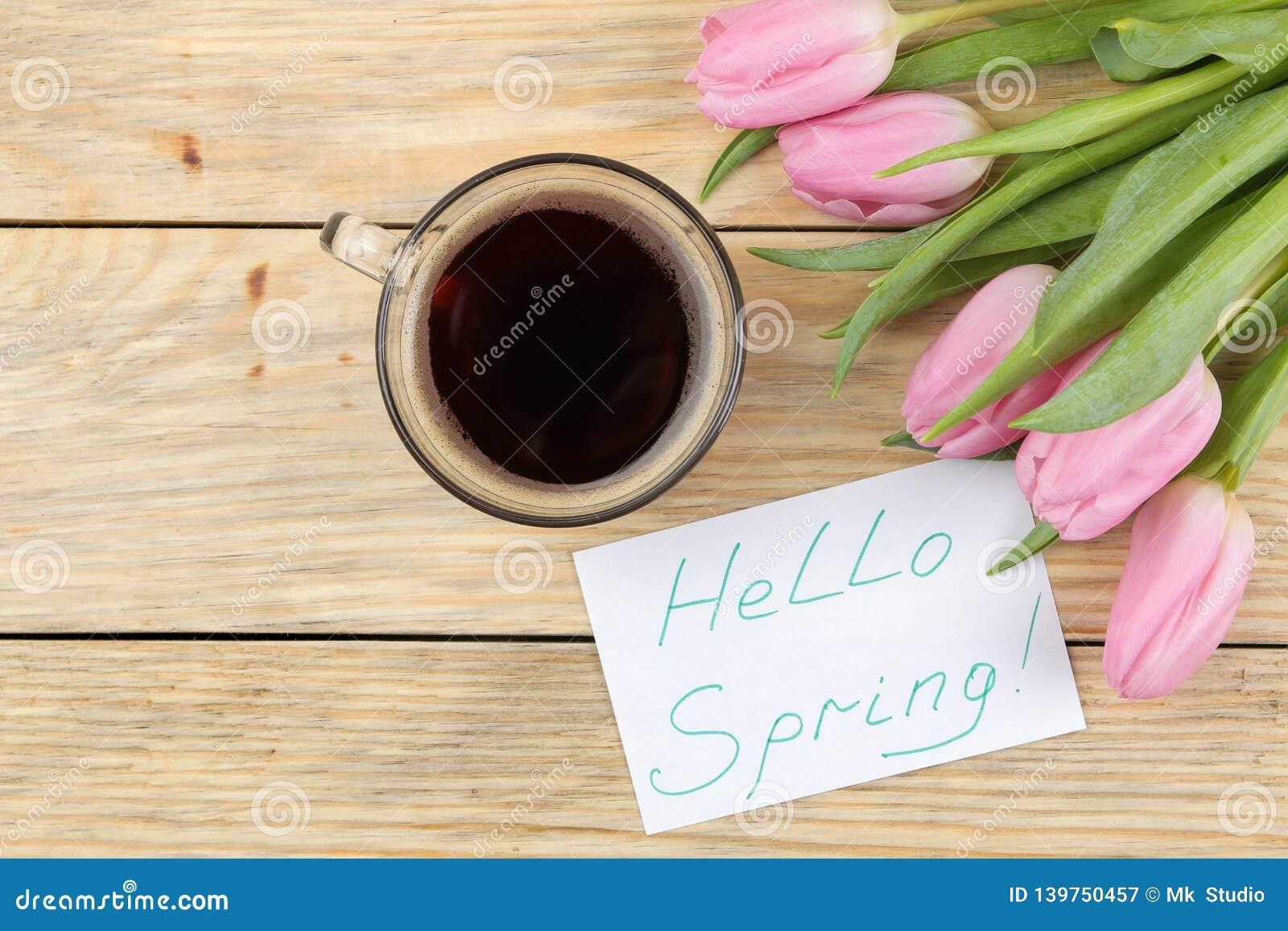 Het mooie boeket van bloemen van roze tulpen, een kop van koffie en de tekst hello springen op papier op een natuurlijke houten a