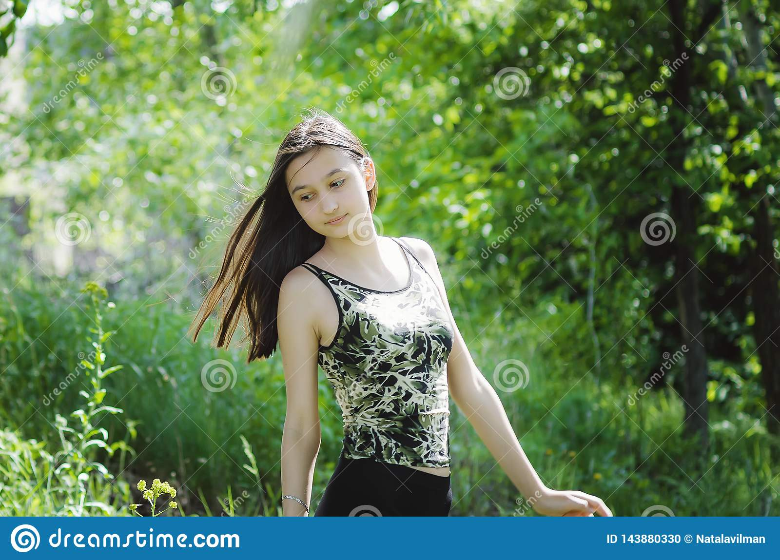 Het mooie brunette van het tienermeisje met lang haar op een achtergrond van de zomeraard