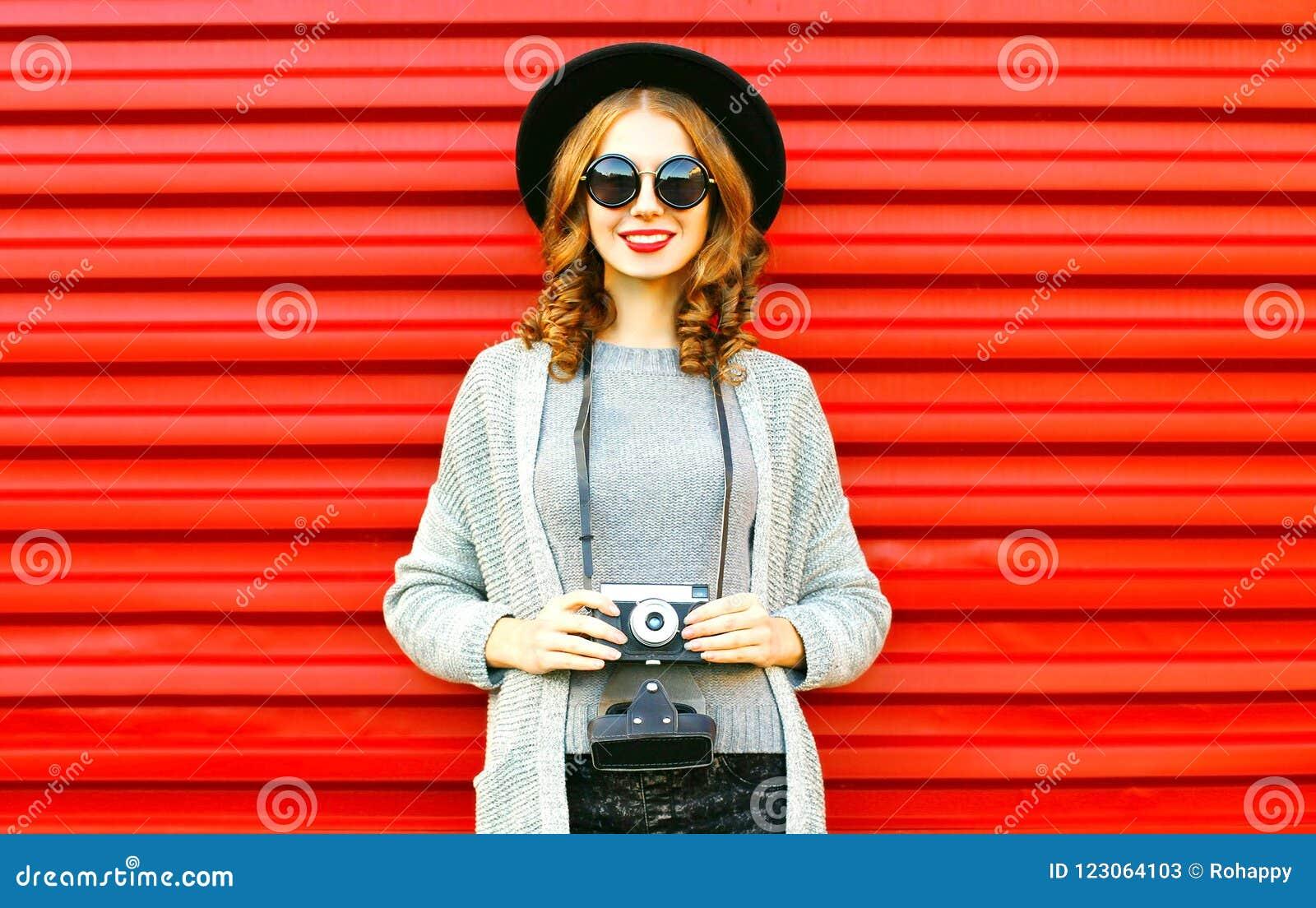 Het mooie de herfst gelukkige meisje houdt retro camera op rode achtergrond