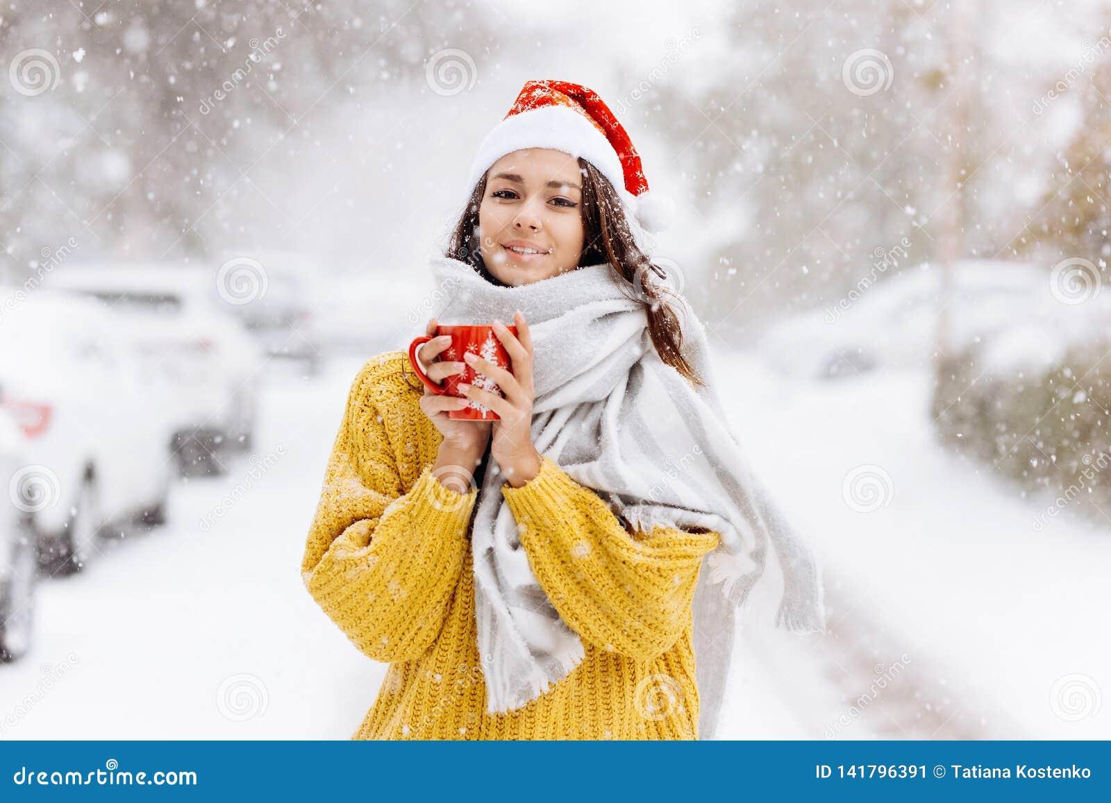 Het mooie donker-haired meisje in een gele sweater, een witte sjaal in Santa Claus-hoed bevindt zich met een rode mok op sneeuw