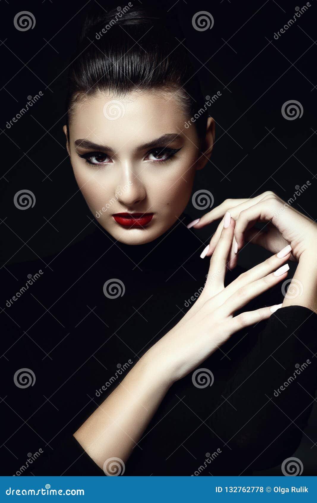 Het mooie donkere die haired model met provocatief maakt omhoog en haar terug in een hoog die broodje wordt geschaafd op zwarte a