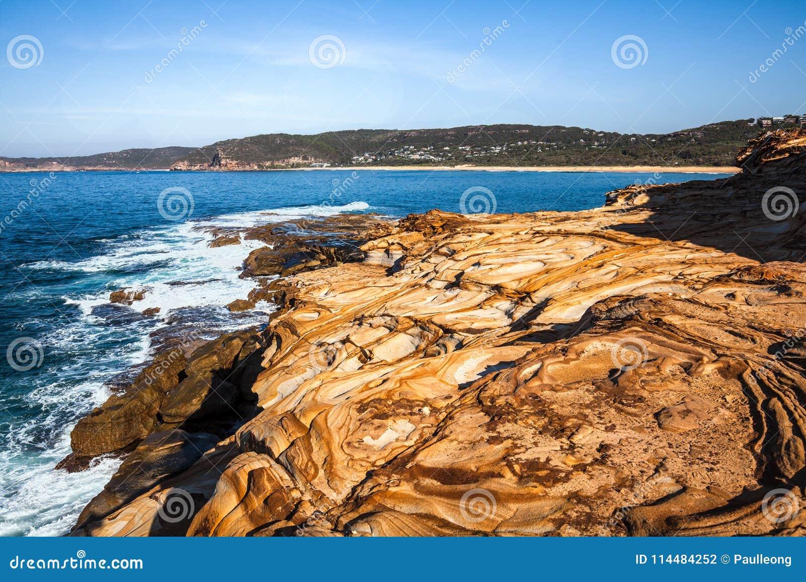 Het mooie gekleurde zandsteen schommelt dichtbij Stopverfstrand, het Nationale Park van Bouddi, Australië