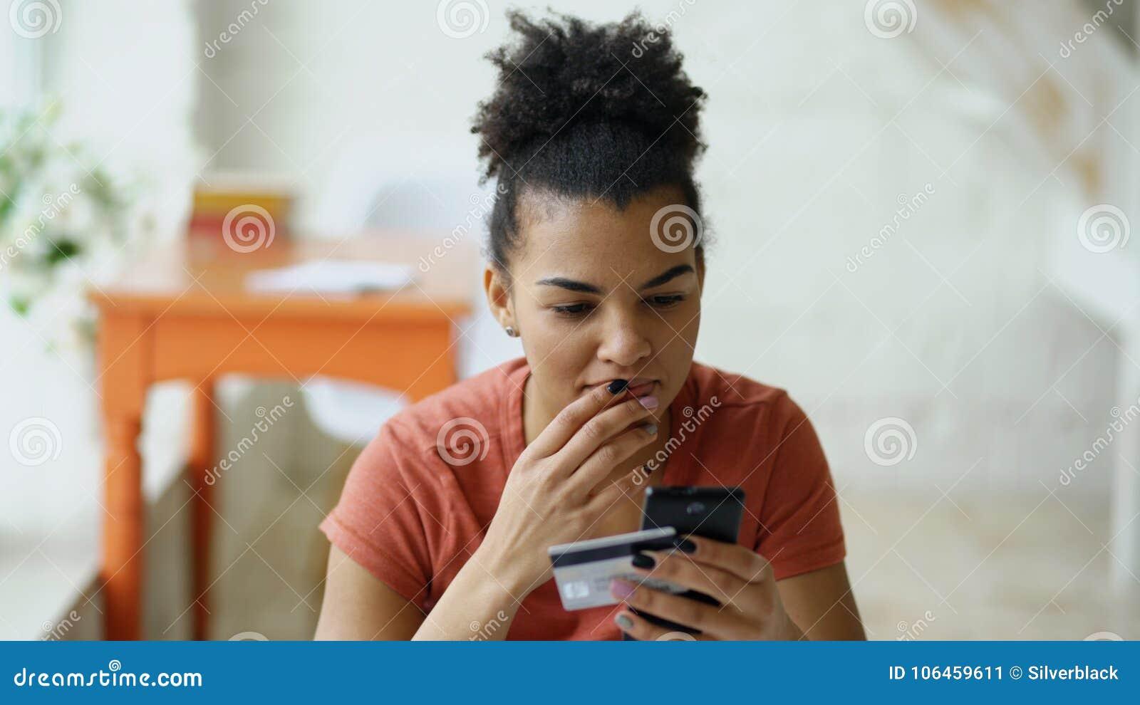 Het mooie gelukkige gemengde online bankwezen die van de rasvrouw smartphone gebruiken die online met creditcard thuis levensstij