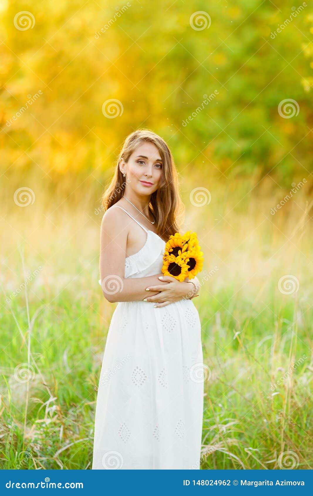 Het mooie gelukkige zwangere meisje op het gebied van madeliefje bloeit in zonsonderganglichten