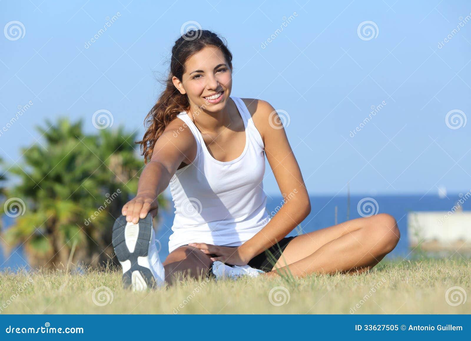 Het mooie geschiktheidsvrouw uitrekken zich openlucht op het gras